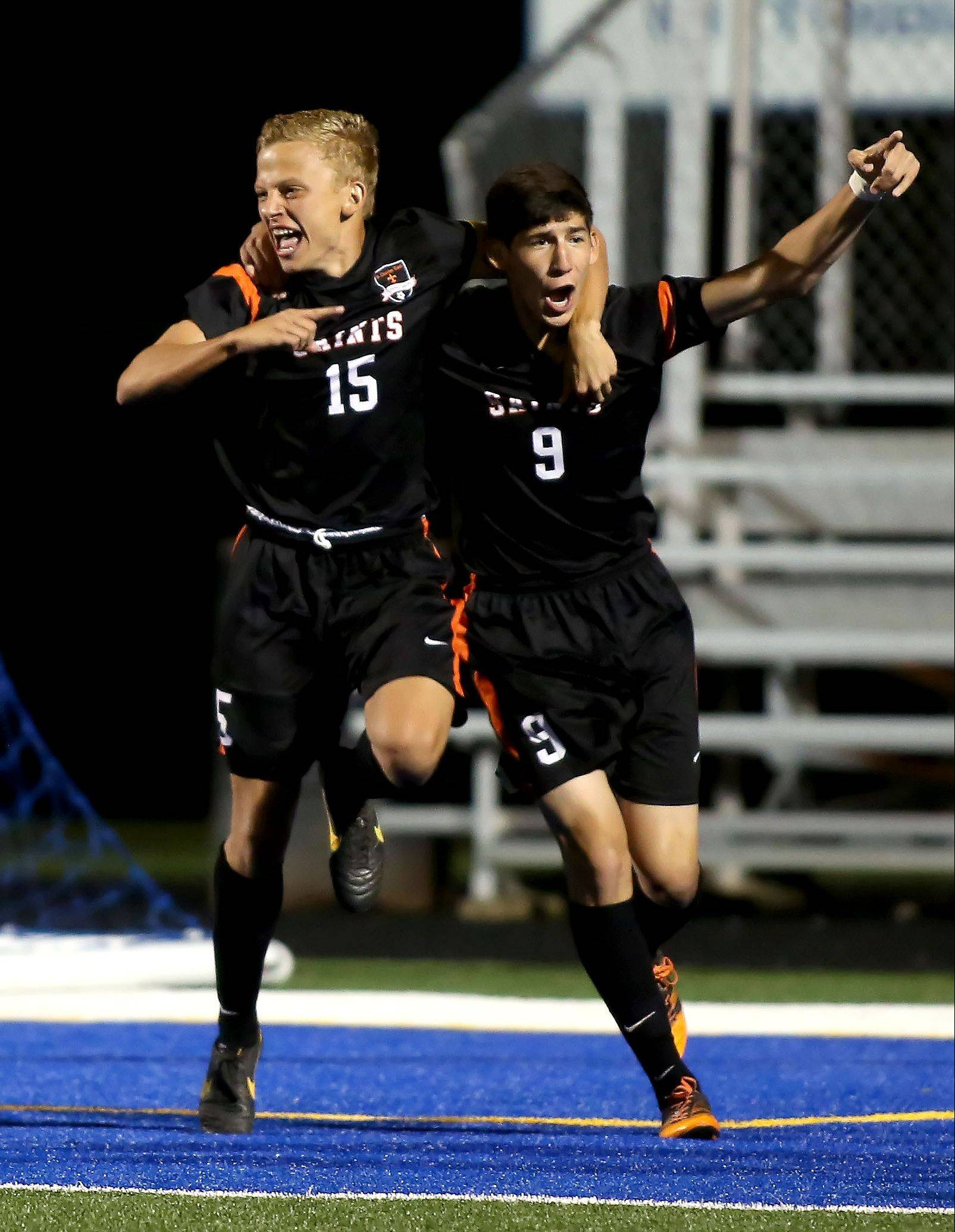 Kevin Heinrich, left and Taylor Ortiz, right, of St. Charles East, celebrate a goal by Heinrich within the first minute of play in Geneva on Tuesday.
