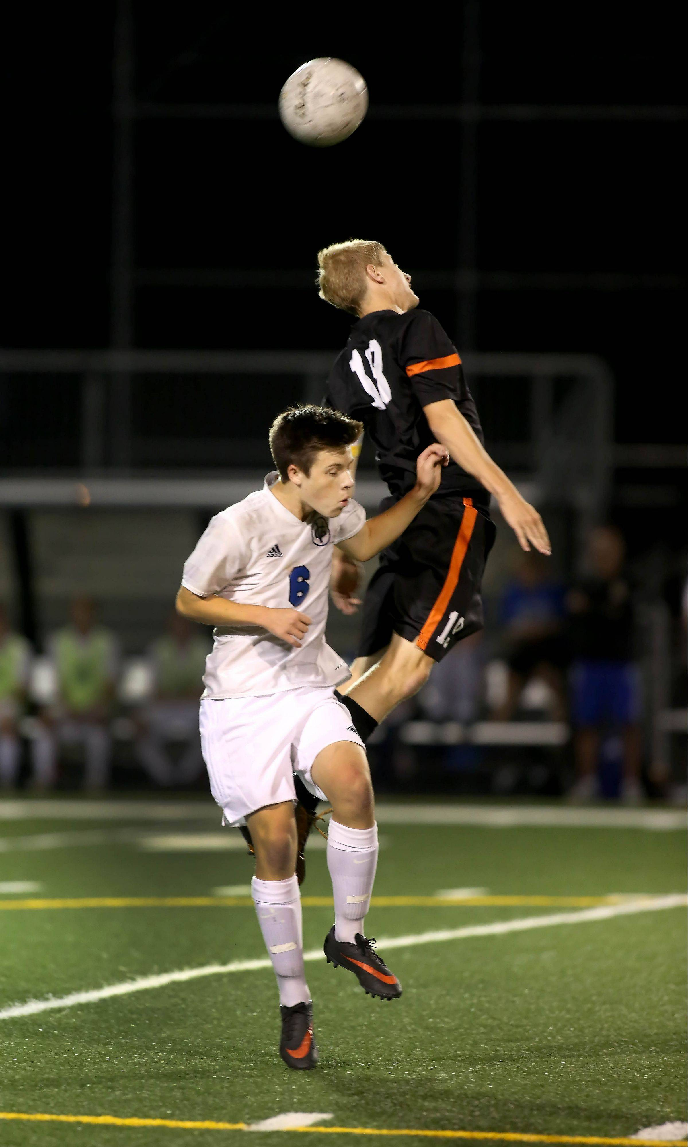 Calen Colbert, left, of Geneva goes up as St. Charles East's Andrew Shone heads the ball away Tuesday.