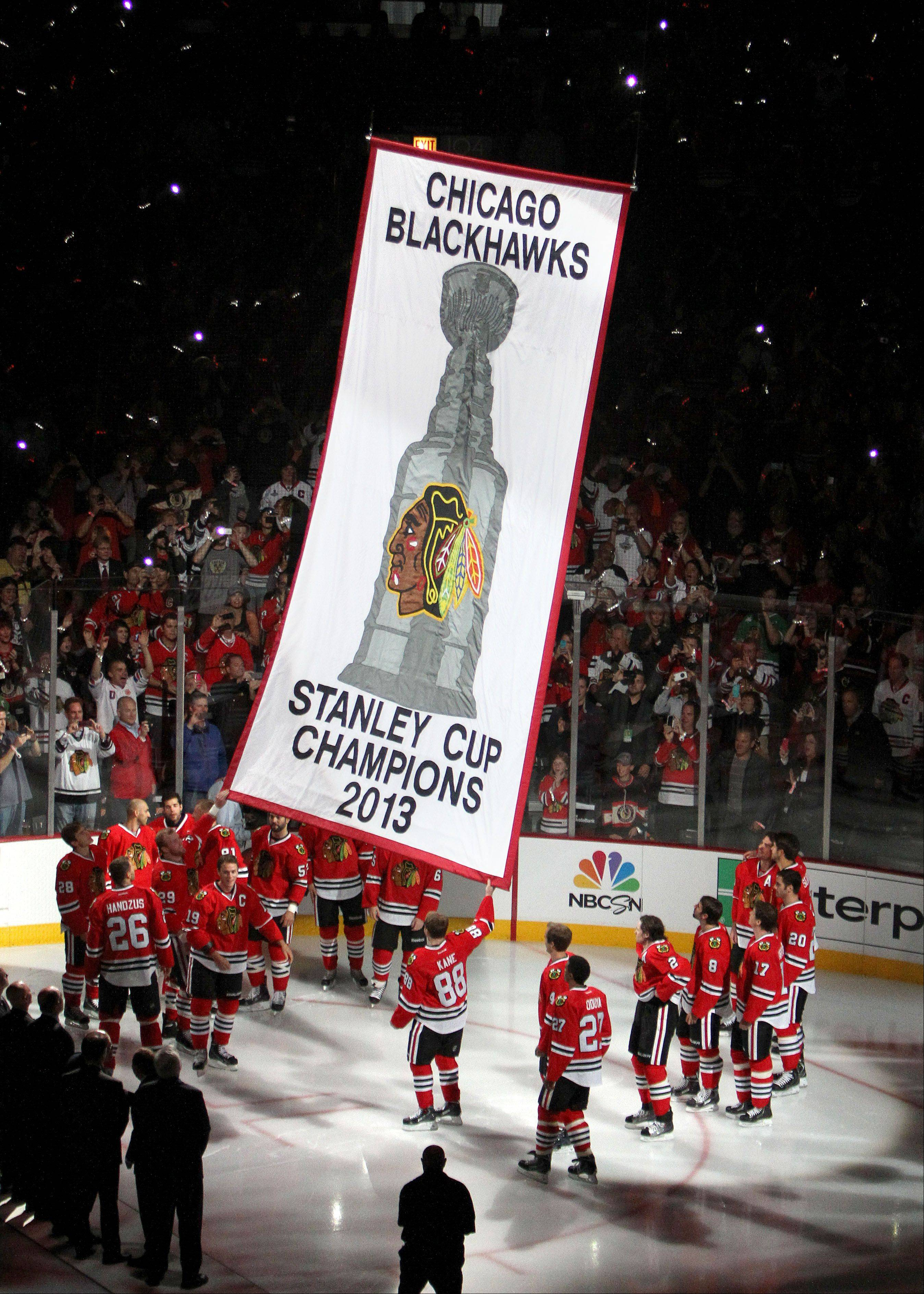 Blackhawks teammates release their 2103 Stanley Cup banner.