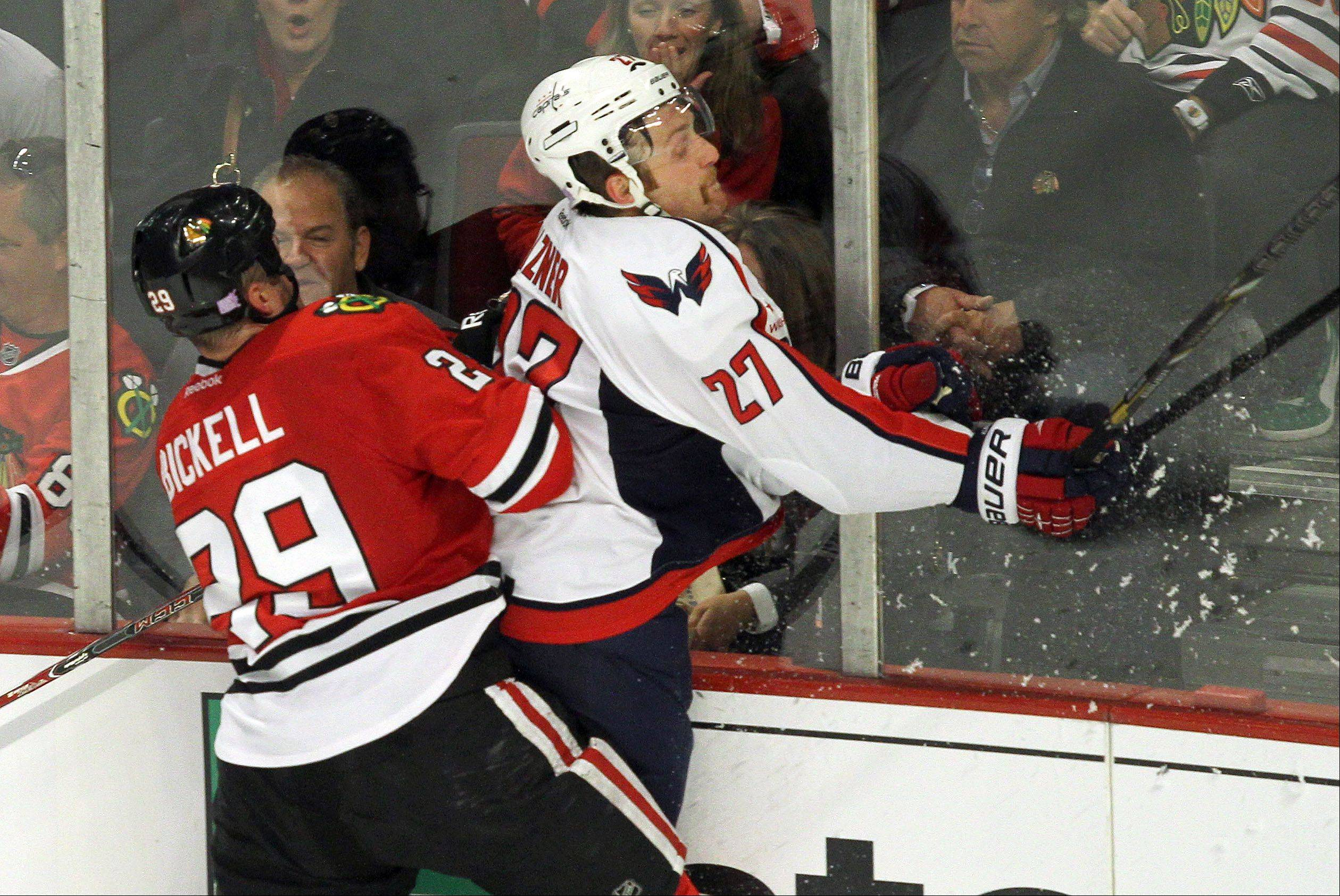 Chicago Blackhawks Bryan Bickell hits Washington Capitals defenseman Karl Alzner.