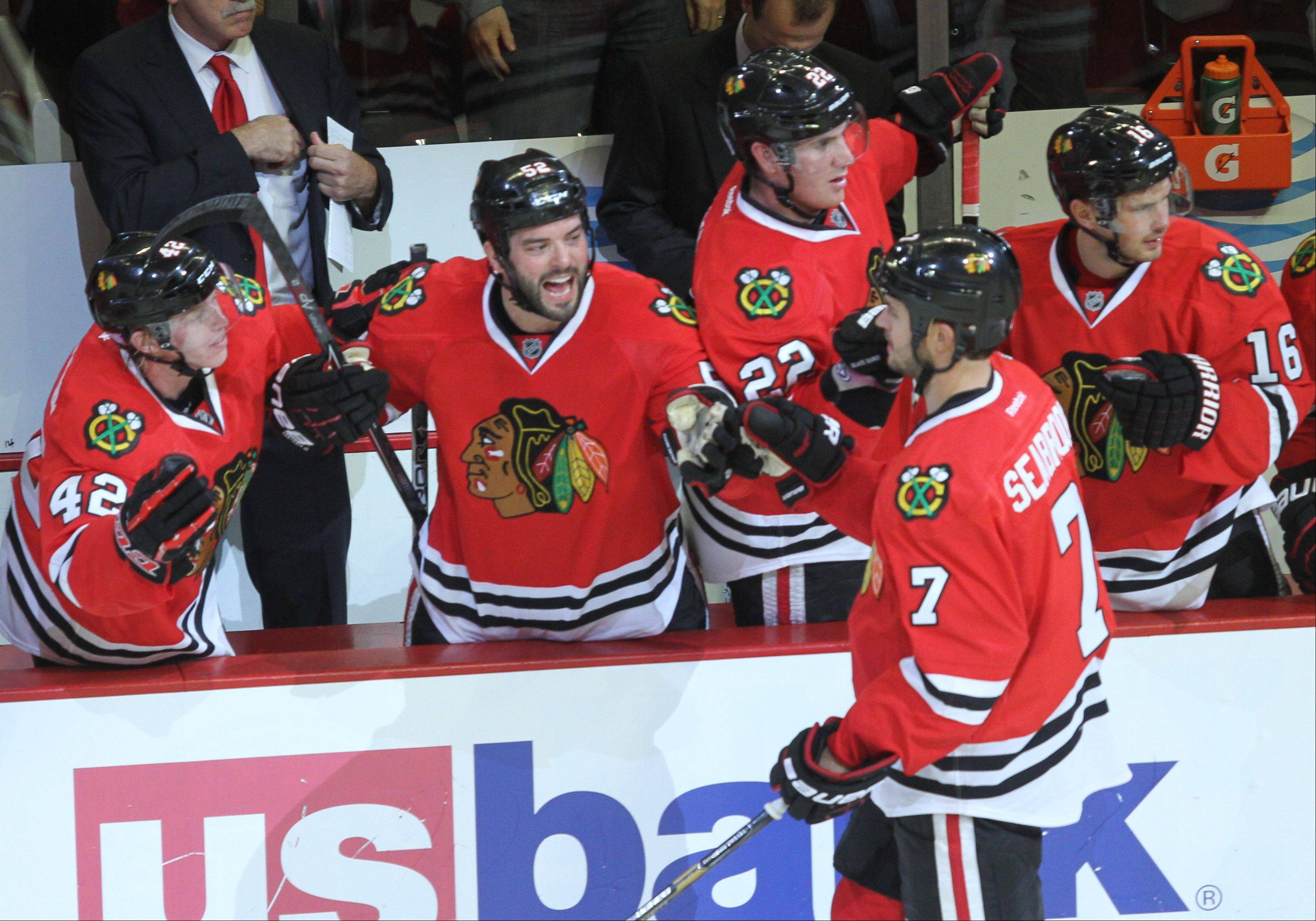 Chicago Blackhawks defenseman Brent Seabrook high-fives teammates after his goal.