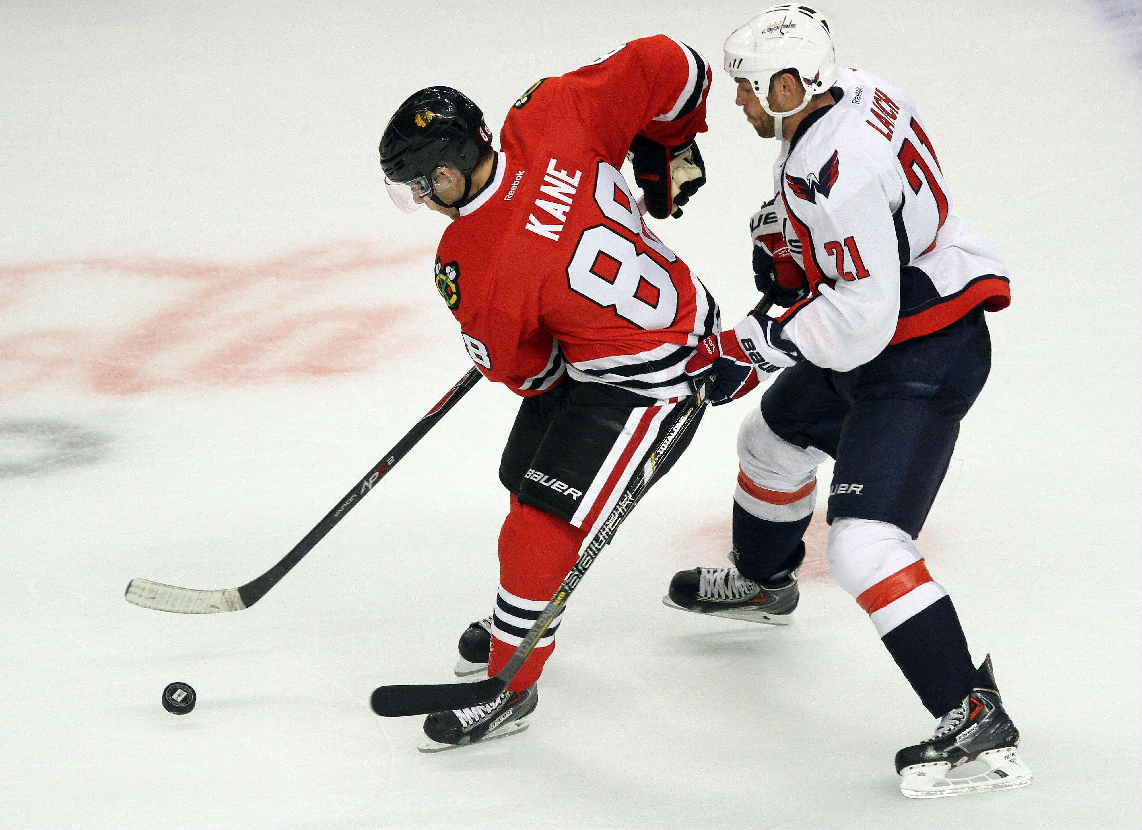 Chicago Blackhawks right wing Patrick Kane drives on Washington Capitals center Brooks Laich.