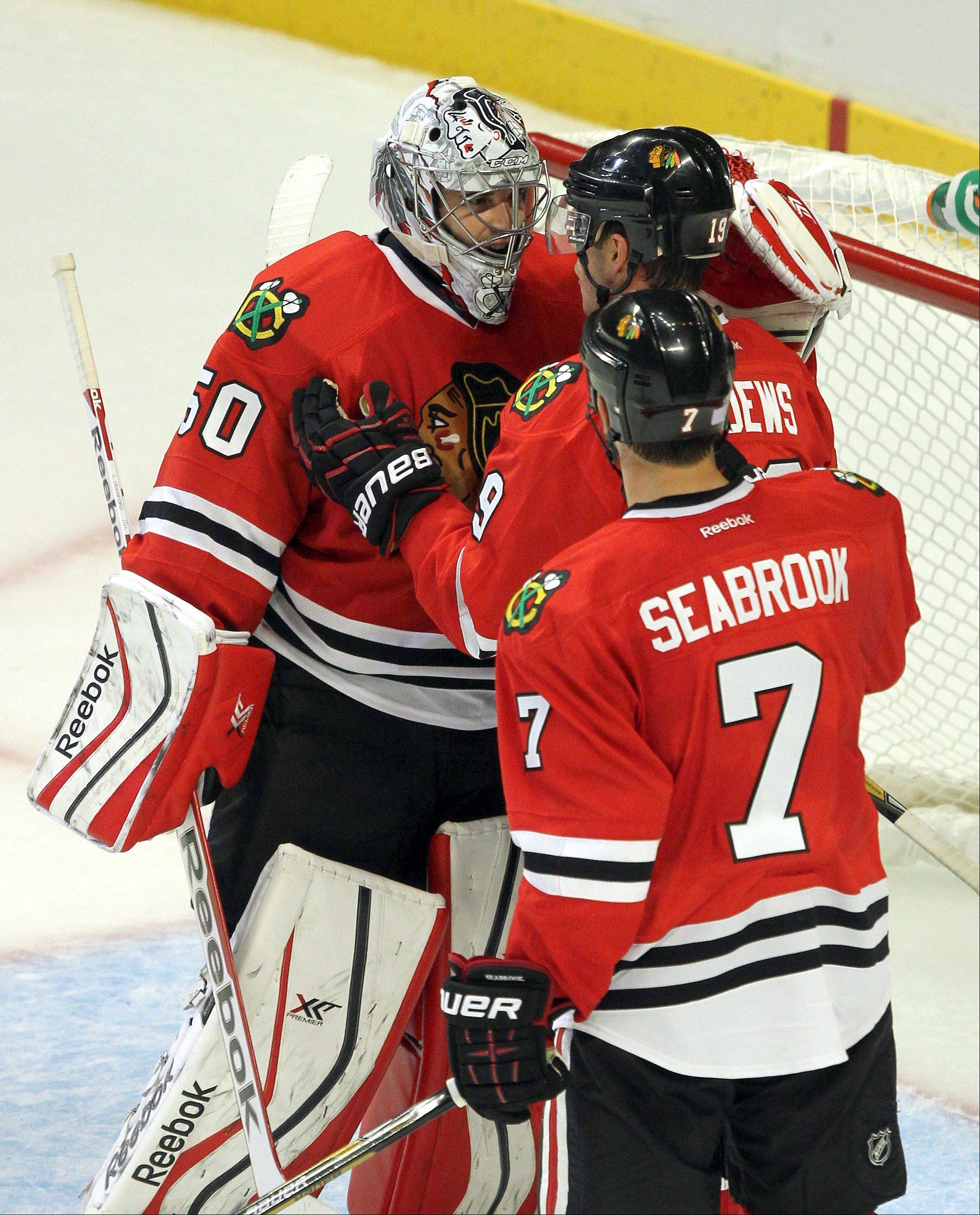 Chicago Blackhawks center Jonathan Toews and Brent Seabrook celebrate with Chicago Blackhawks goalie Corey Crawford .