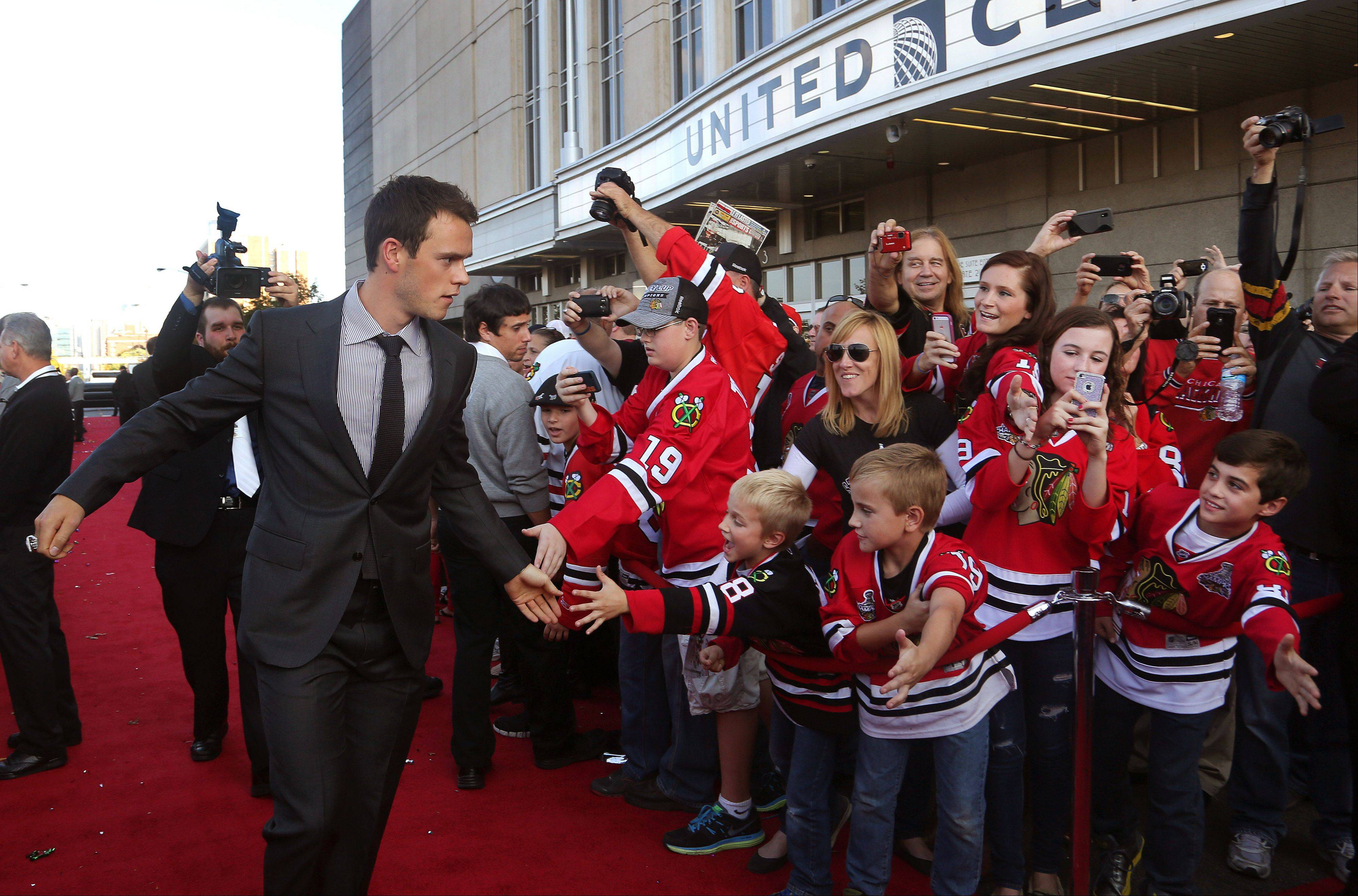 Chicago Blackhawks center Jonathan Toews high-fives fans.