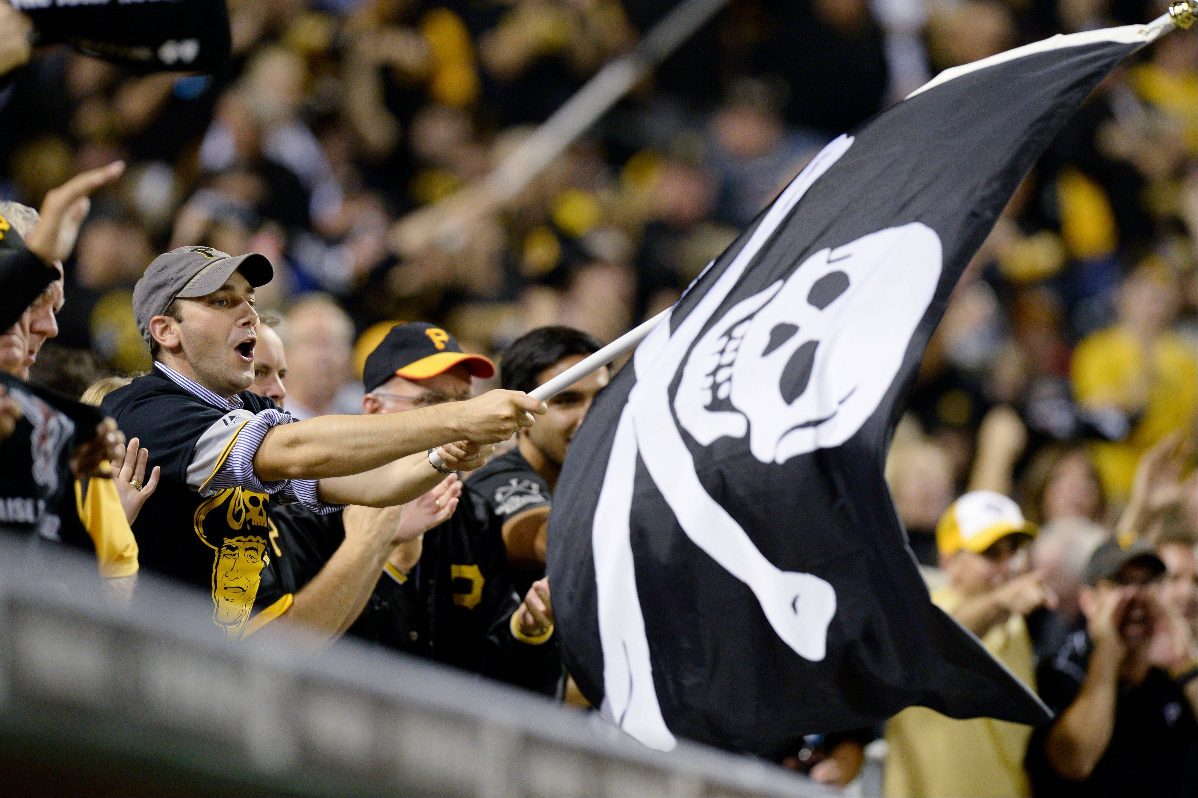 A Pittsburgh Pirates fan waves a Jolly Roger flag as the Pirates play the Cincinnati Reds in the NL wild-card playoff baseball game Tuesday, Oct. 1, 2013, in Pittsburgh.
