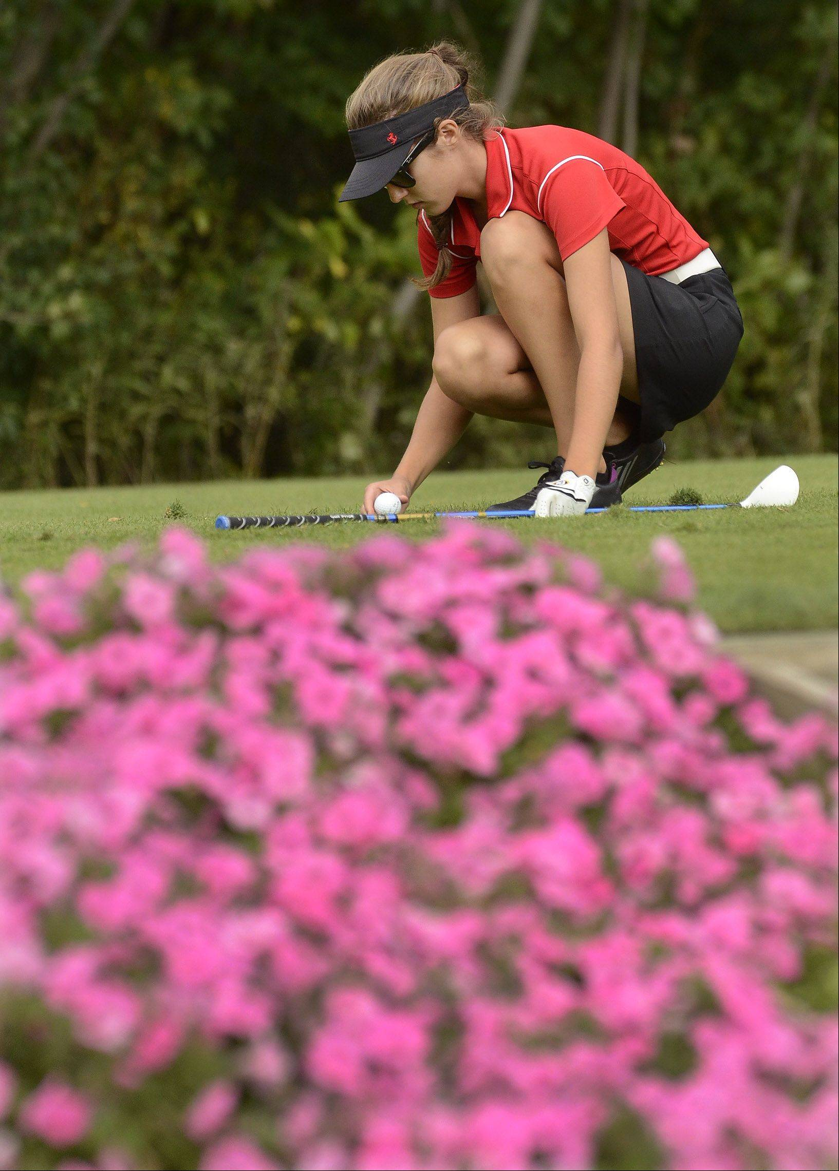 Courteney Fabbri of Mundelein tees up her ball on the par-3 13th hole during the North Suburban Conference girls golf meet at Deerpath Golf Course in Lake Forest.