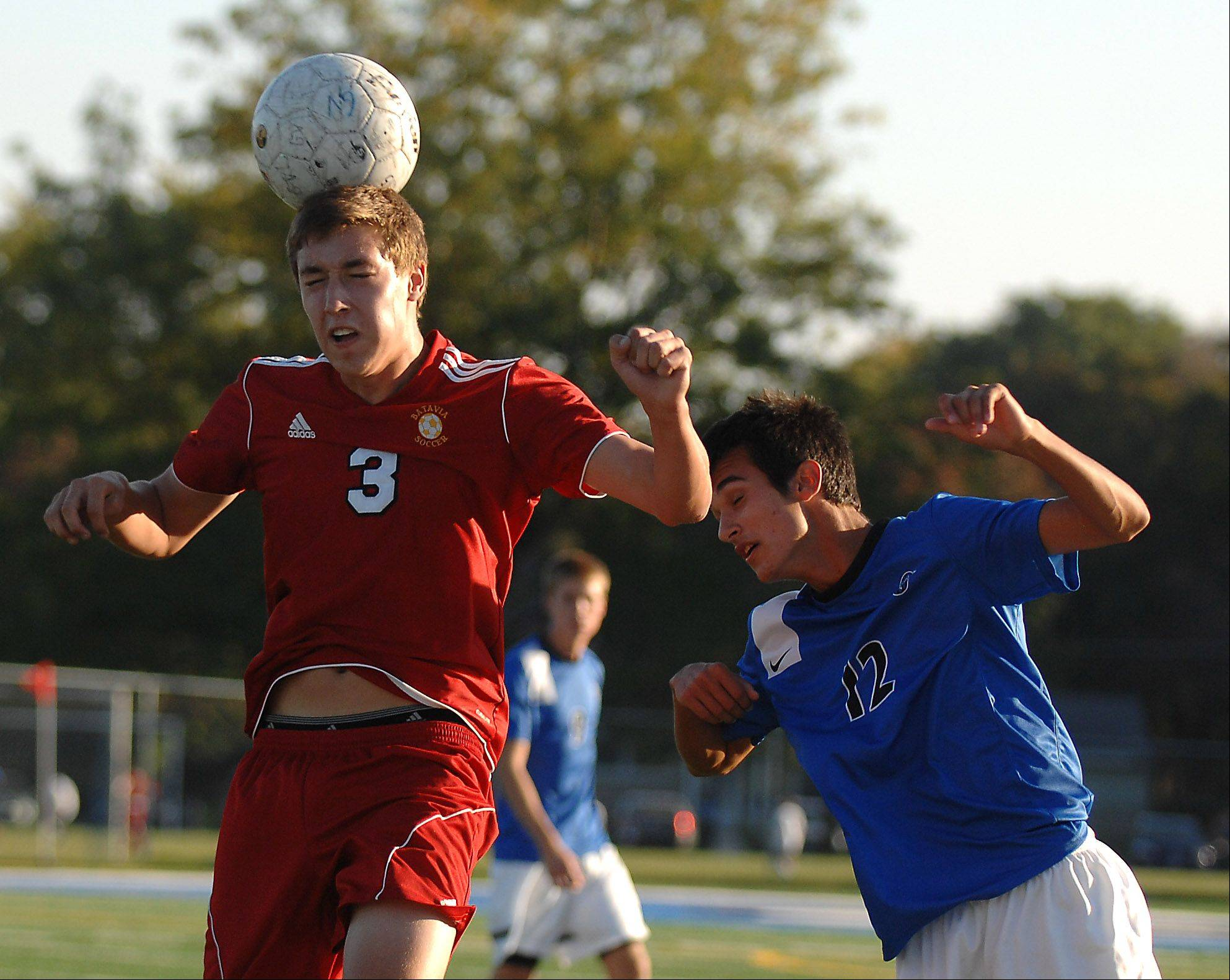 Batavia's Kevin Collins flicks a header on while being defended by St. Charles North's Jake Kerr during Tuesday's action at the Tri-Cities boys soccer challenge in Geneva.