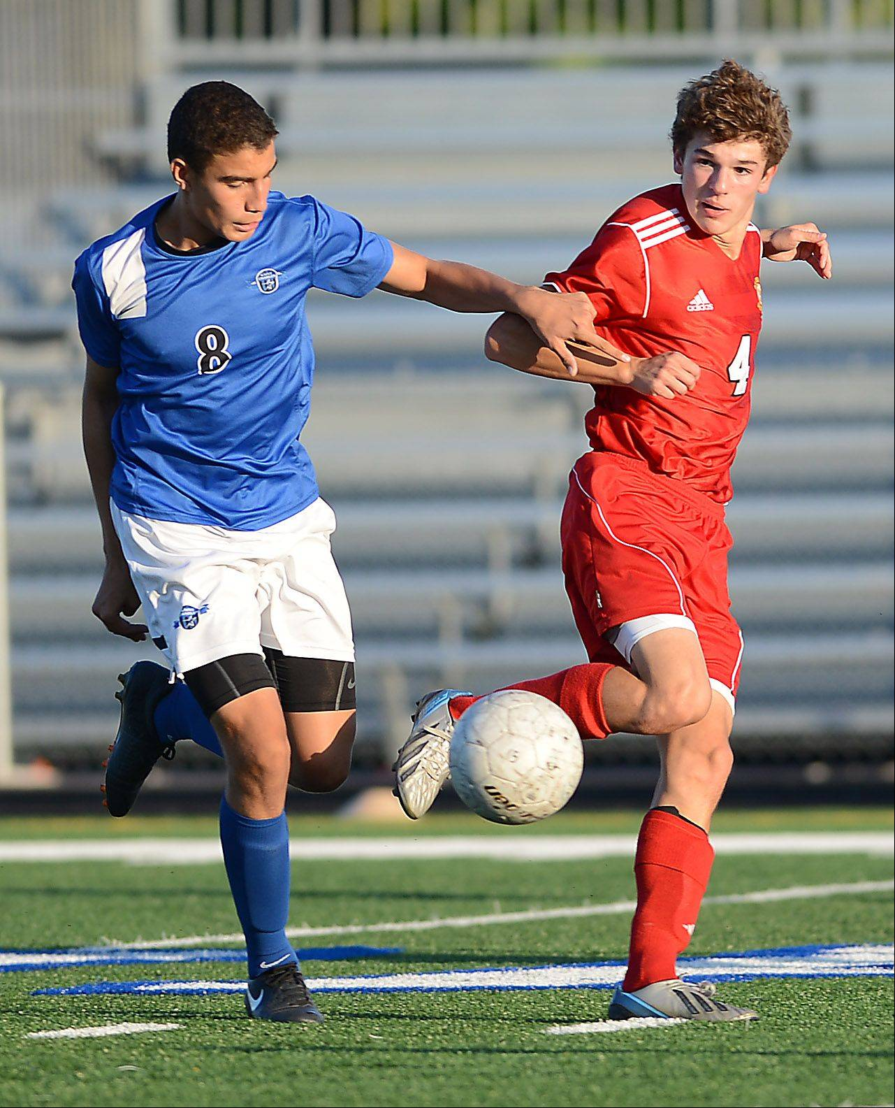St. Charles North's Lorenzo Estrada and Batavia's Nathan Carey battle for the ball during Tuesday's action at the Tri-Cities boys soccer challenge in Geneva.