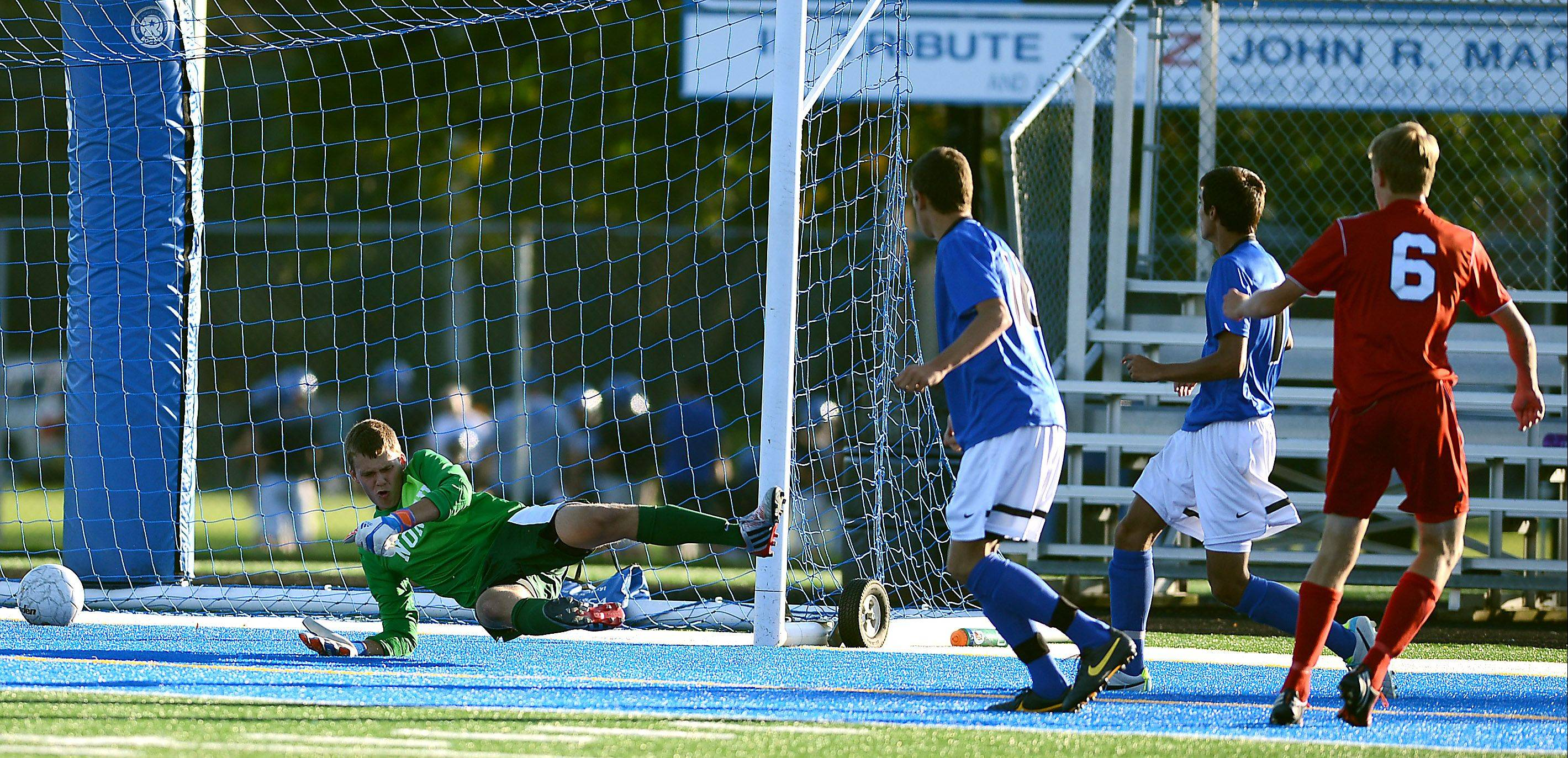 Batavia's Ian Larson (6) slides a shot past St. Charles North's Billy Larsen for the game-winning goal Tuesday in Geneva.