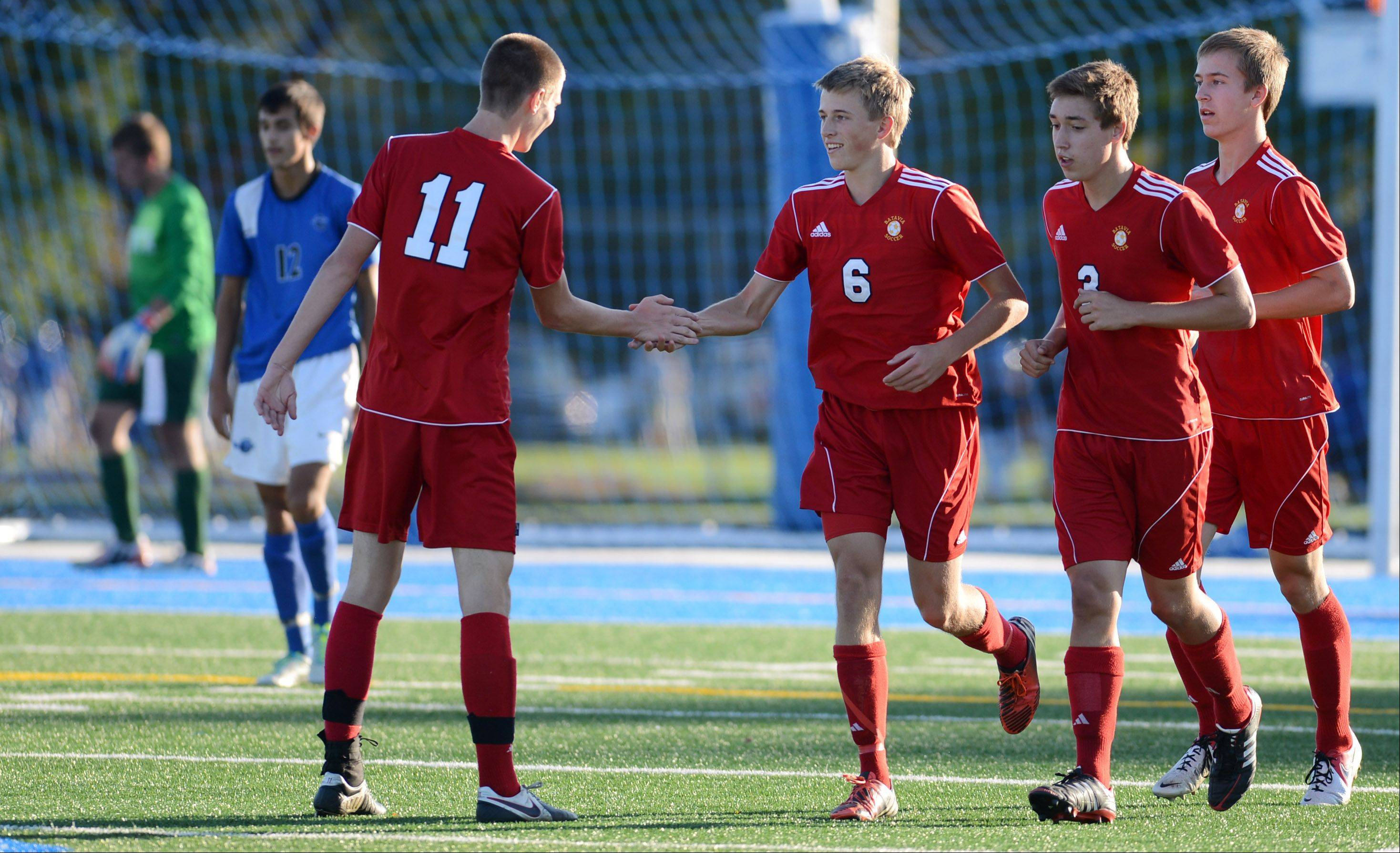 Batavia teammates, including John Barnes (11), congratulate Ian Larson after his goal against St. Charles North during Tuesday's action at the Tri-Cities boys soccer challenge in Geneva.