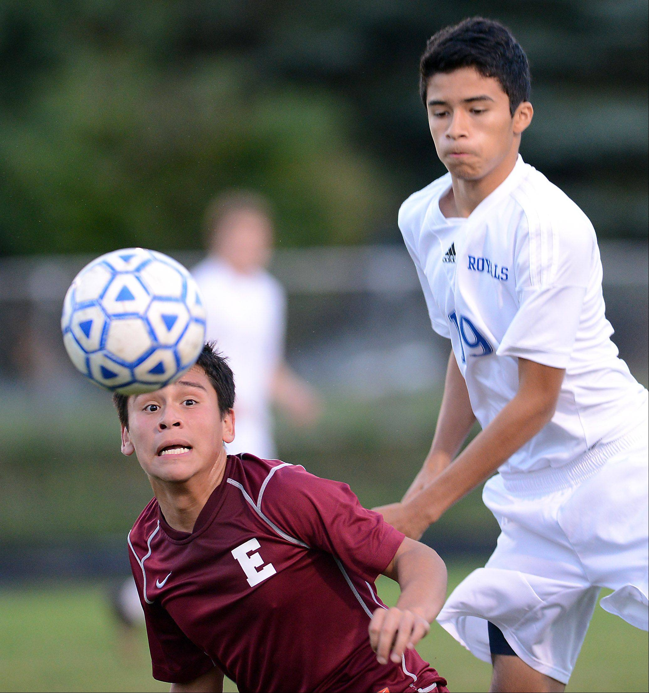 Elgin's Joel Chavez keeps his eyes on the ball with a Larkin defender coming over his back during Tuesday's game at Memorial Field in Elgin.