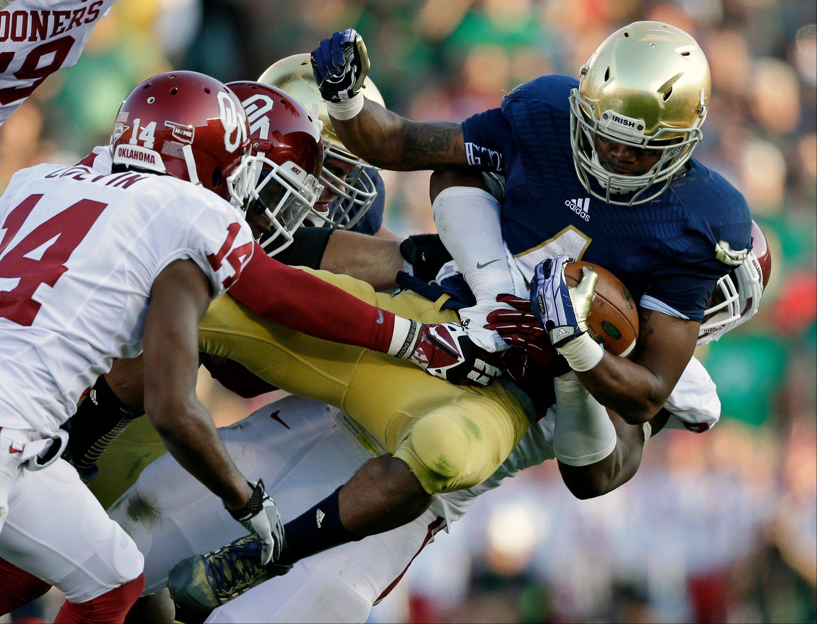 Notre Dame's George Atkinson III is tackled by Oklahoma's Geneo Grissom during the second half of Saturday's game in South Bend, Ind. Oklahoma defeated Notre Dame 35-21.