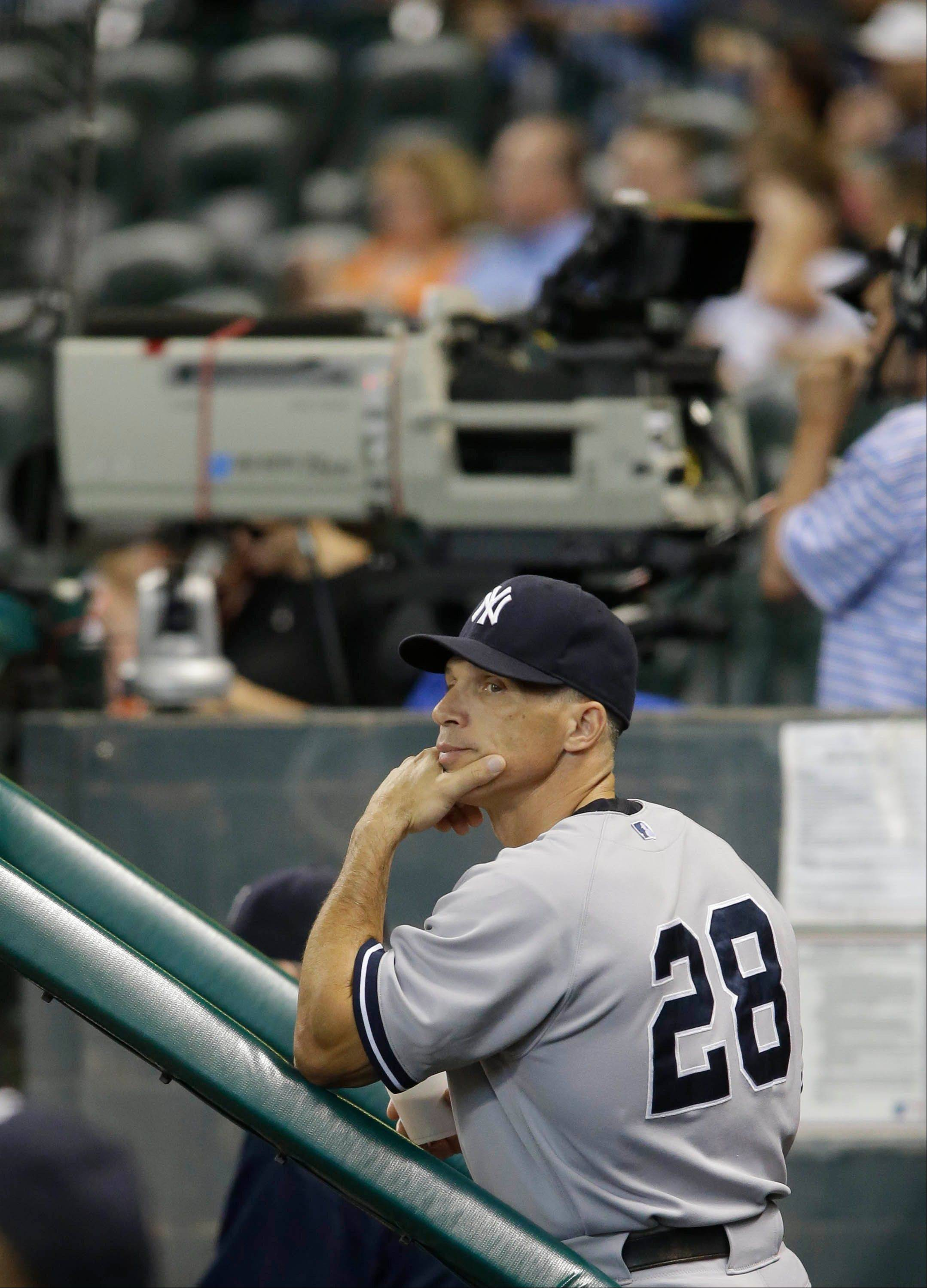 New York Yankees manager Joe Girardi watches the scoreboard from the dugout during Sunday's game in Houston.