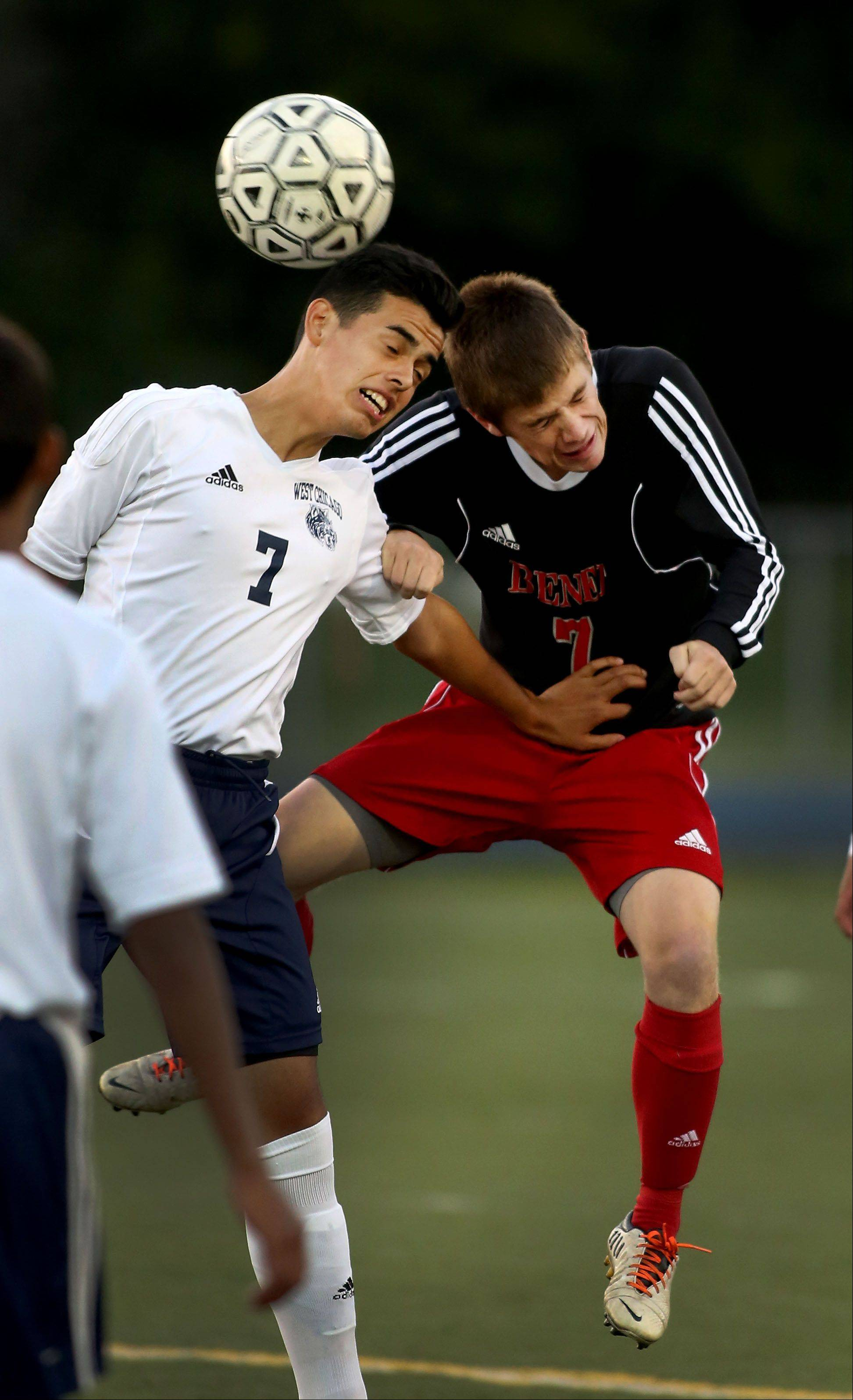 Benet Academy's Sam Knapke, right, heads the ball away from West Chicago's Alexis Quezada during boys soccer action on Monday.