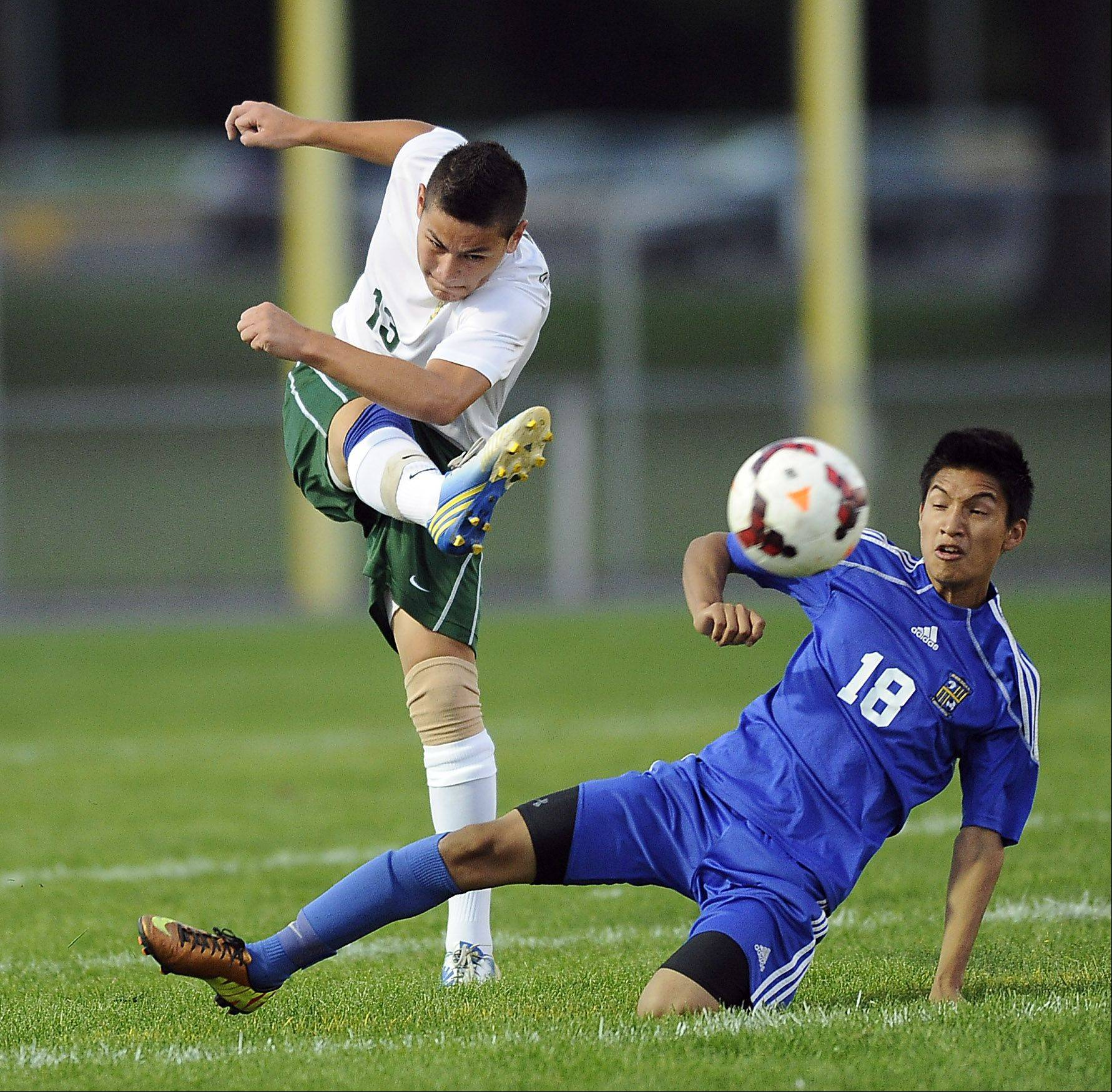 Elk Grove's Arnold Aguilar and Wheeling's Elias Cisneros battle for the ball during Thursday's soccer game in Elk Grove Village.