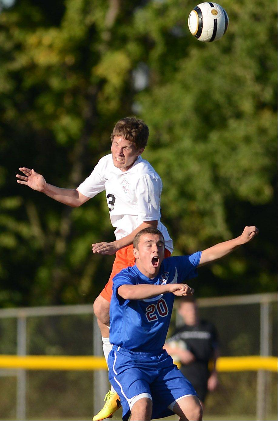St. Charles East's Jared Brown goes up to win a header over Marmion's Nicholas Grant during Thursday's game in St. Charles.