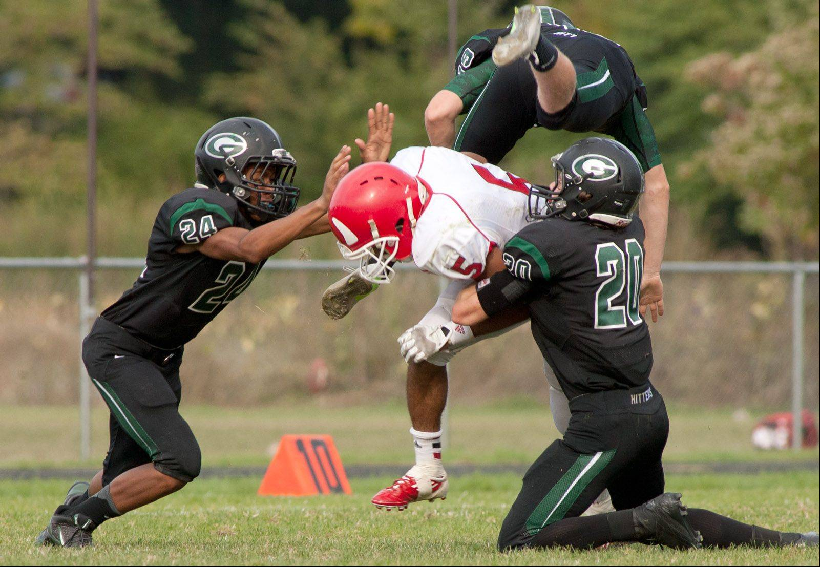 Hinsdale Central's Juwan Edmund, center, is tackled by Glenbard West's Ryan Thomas, left, and Jason Balogh.
