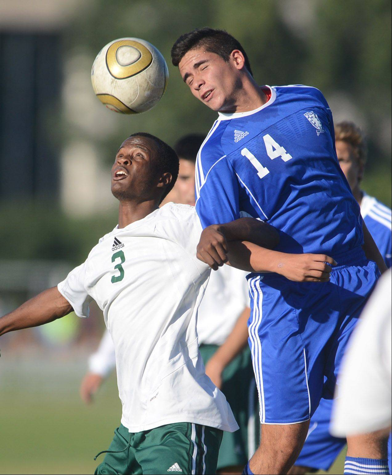 Stevenson's Kamal Starks (3) keeps a sharp eye on the ball under pressure from Lake Zurich's Miguel Hernandez during Monday's soccer game in Vernon Hills.