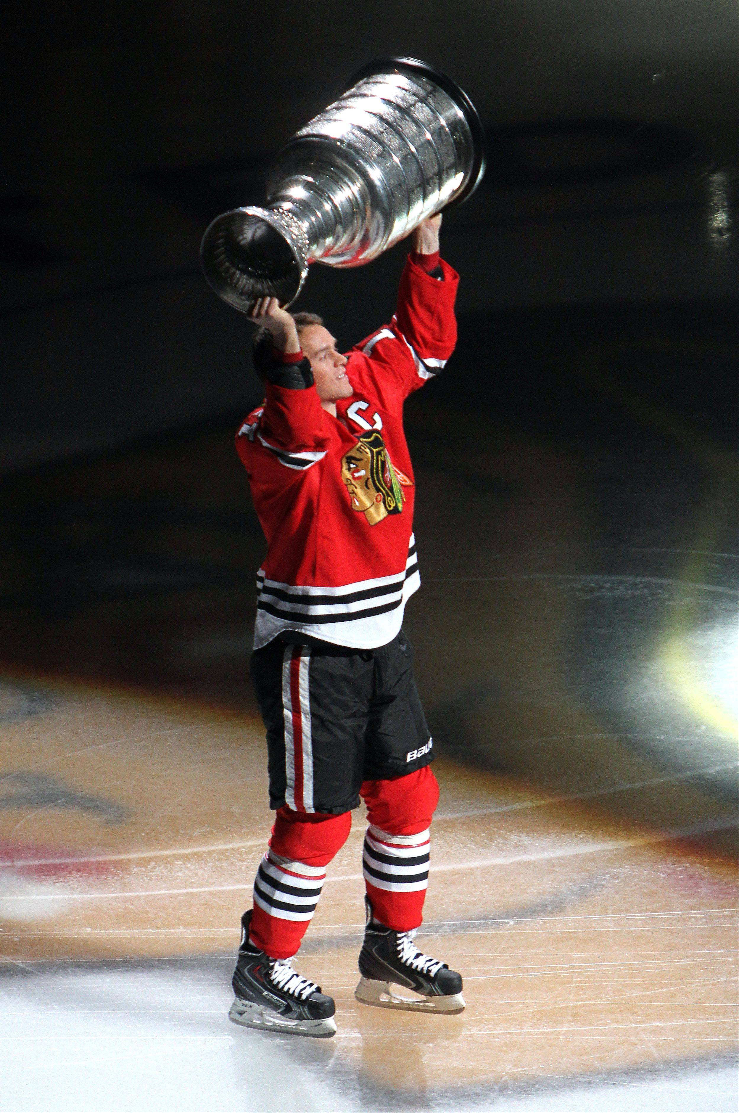 Steve Lundy/slundy@dailyherald.comChicago Blackhawks center Jonathan Toews carries the Stanley Cup over his head during a banner ceremony prior to their opening-day-game against the Washington Capitals Tuesday at the United Center in Chicago.