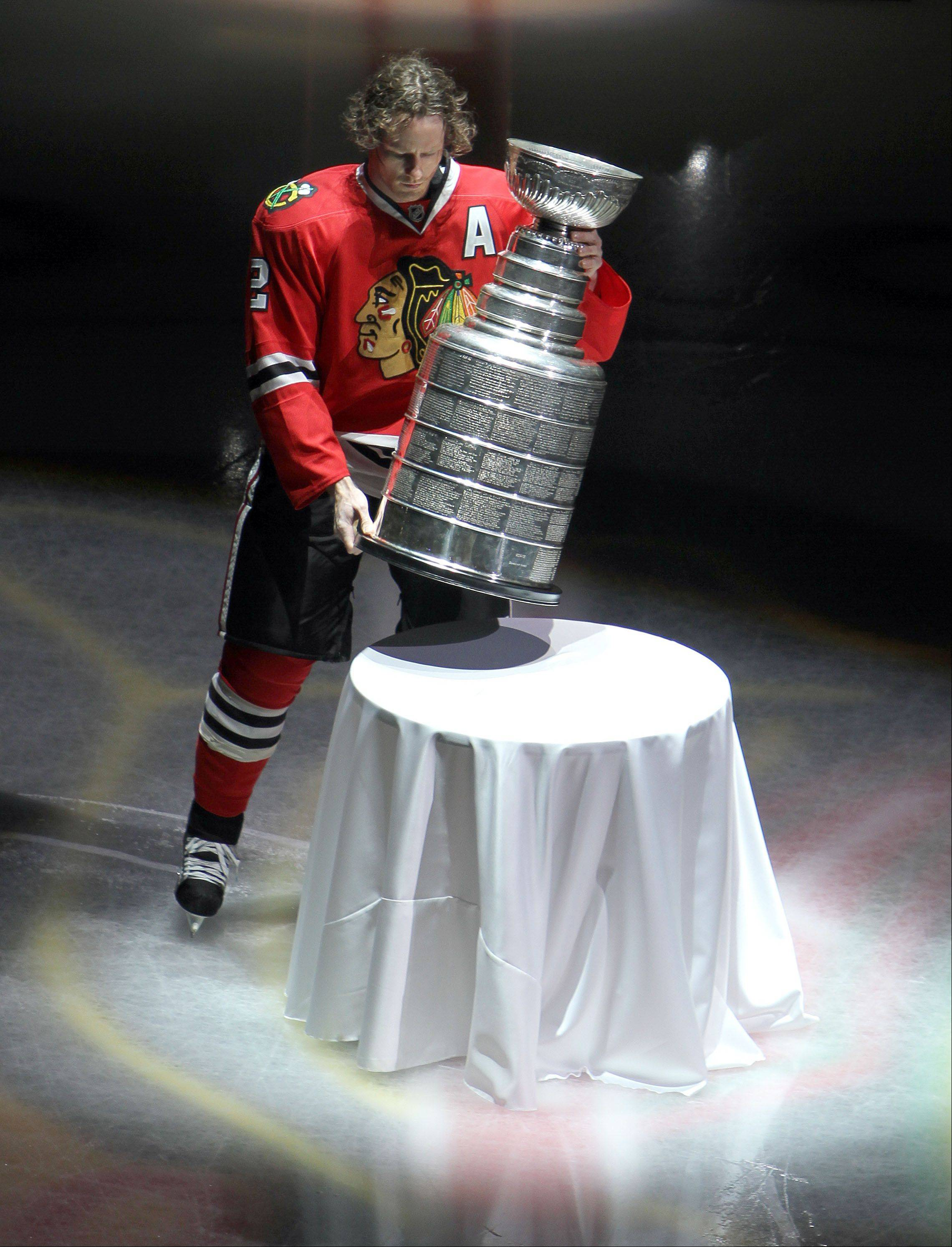 Steve Lundy/slundy@dailyherald.comChicago Blackhawks defenseman Duncan Keith carries in the Stanley Cup during the banner ceremony prior to their opening-day-game against the Washington Capitals Tuesday at the United Center in Chicago.