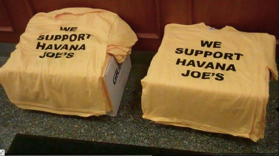 "Supporters of a proposed cigar shop wore T-shirts reading ""We Support Havan Joe's"" to the Mount Prospect village board meeting this week. Several other residents, however, appeared before the board to oppose the business."