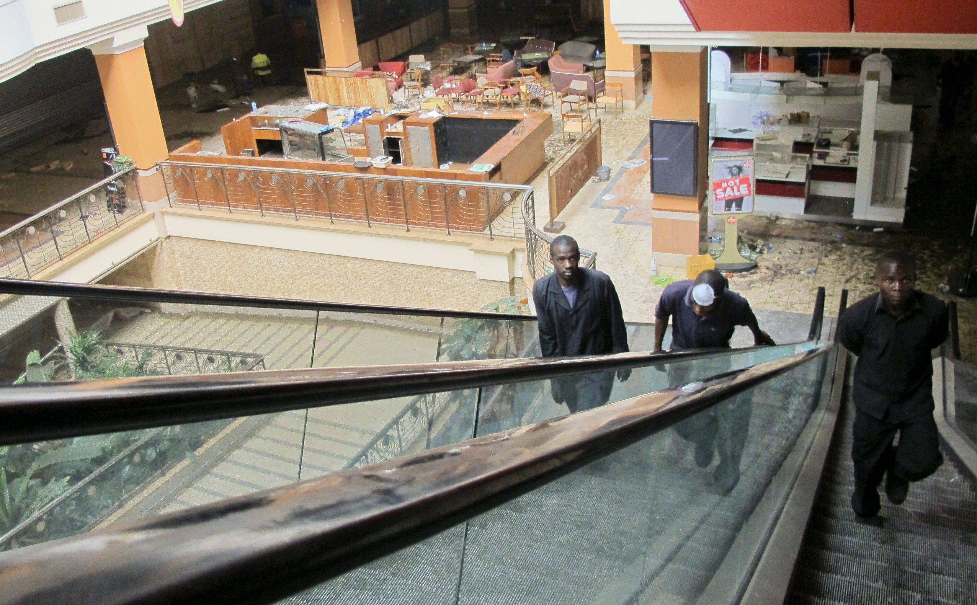 Men walk up the escalators from the ground floor in the Westgate Mall in Nairobi, Kenya Tuesday, Oct. 1, 2013. A top Kenya government official says four armed assailants can be seen on closed circuit television footage during the terrorist attack on an upscale mall in which at least 67 people were killed, an indication that there may not have been as many attackers as initially believed.