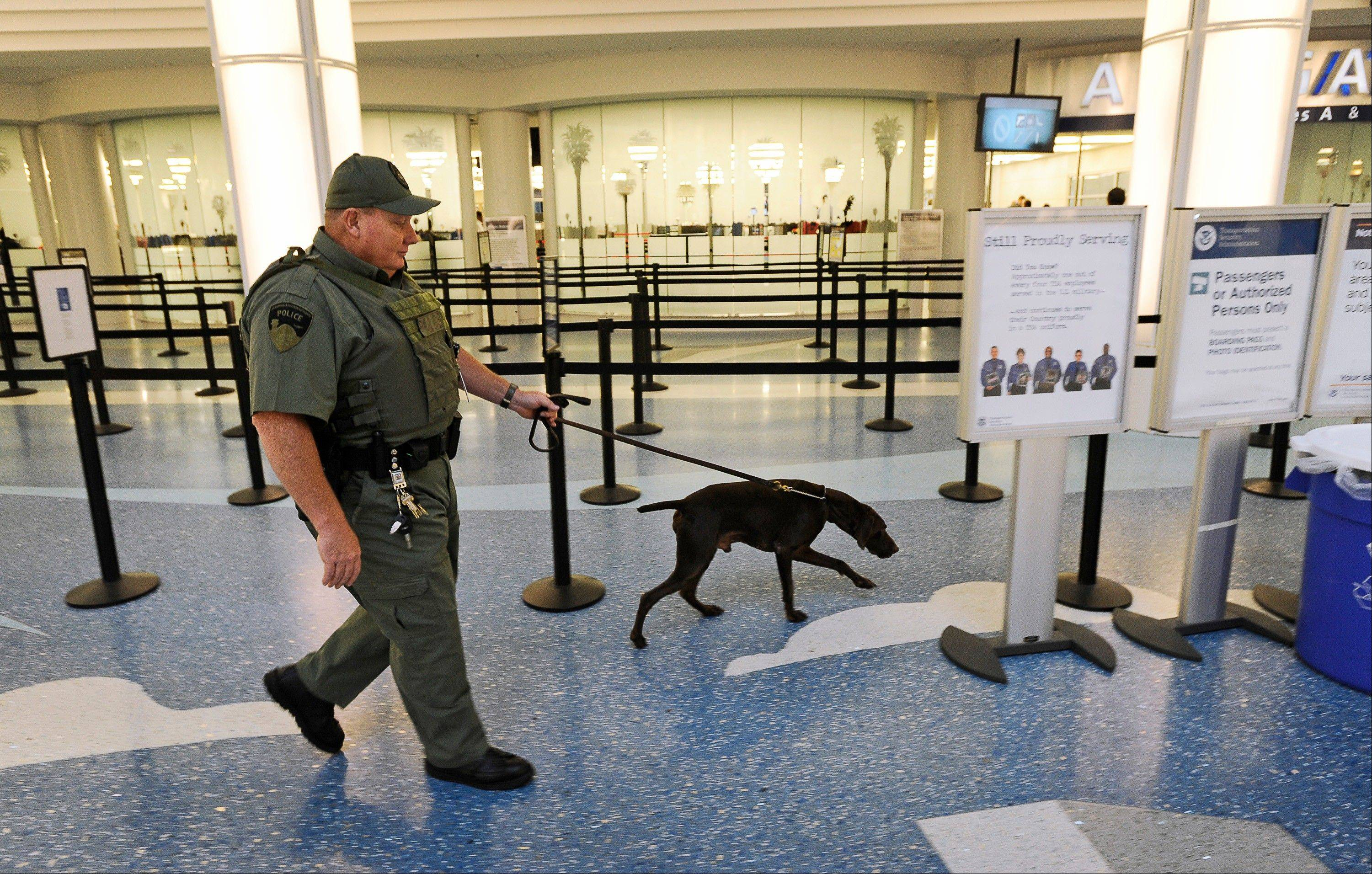 "Jacksonville International Airport police officer Tim Hodges walks around the terminal with a bomb dog at Jacksonville International Airport on Wednesday, Oct. 2, 2013. Authorities said a man arrested at Jacksonville International Airport told security screeners he had a bomb in his backpack but they only found a luggage scale with a microchip inside, along with a remote-control device he called a ""detonator."""
