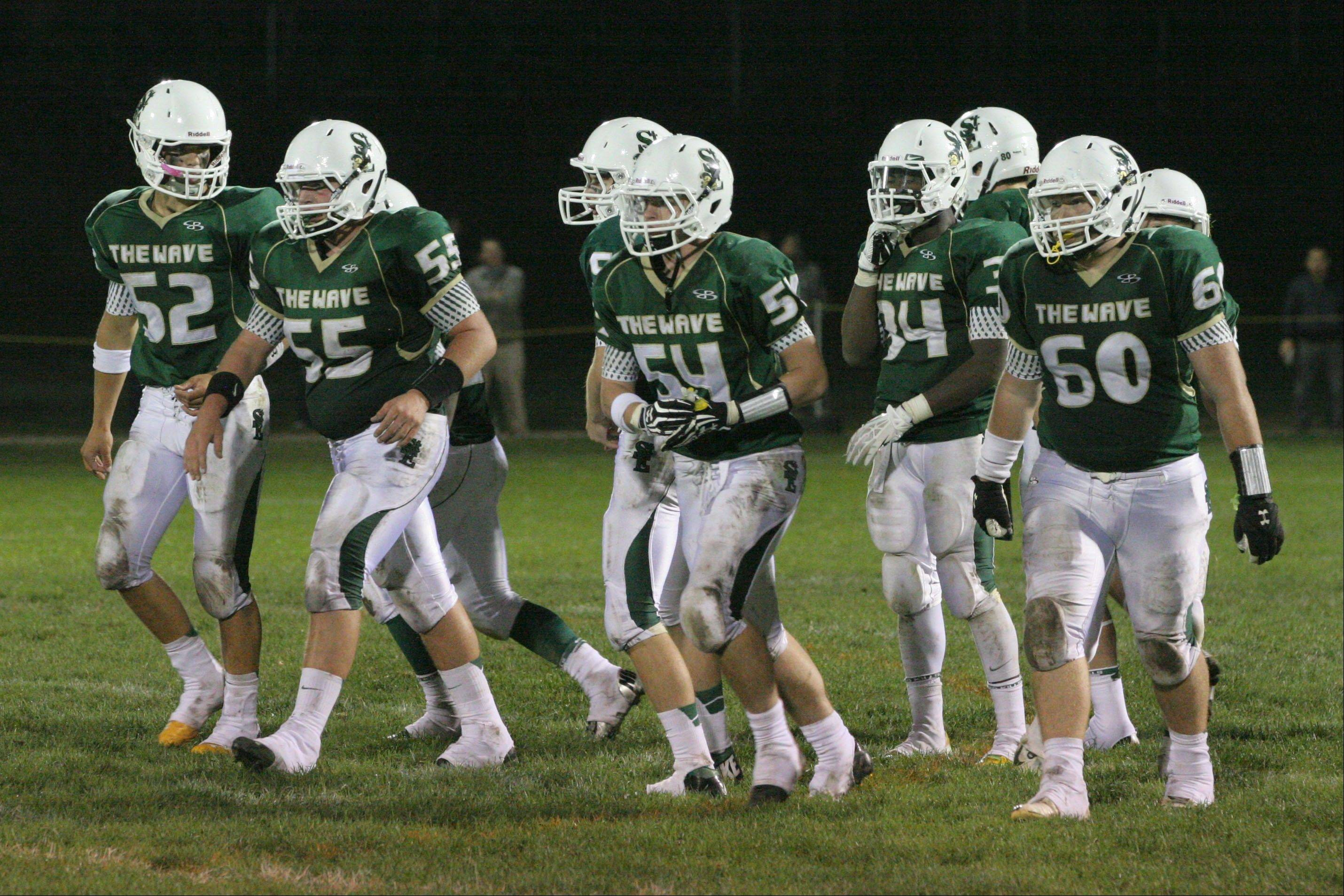 The St. Edward offensive line of Matthew Colasuono, from left, Collin Holte, Jack Tierney and Zach West lead senior running back DaVontae Elam (34) to the line of scrimmage against IC Catholic. St. Edward goes into Friday�s game against Chicago Christian at 3-2 for the season.