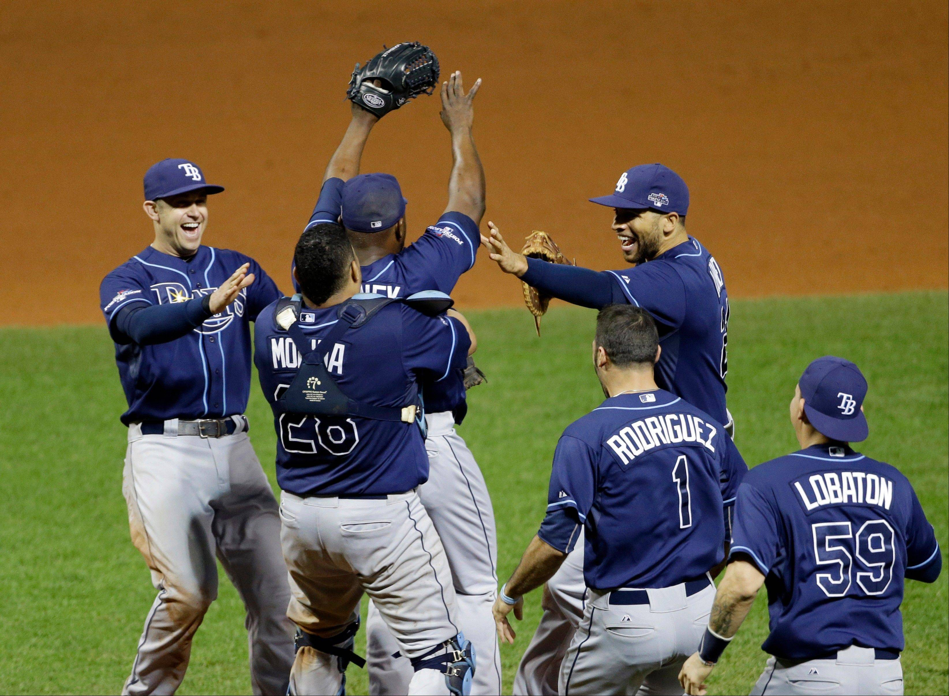 The Tampa Bay Rays celebrate after defeating the Cleveland Indians 4-0 in the AL wild-card baseball game Tuesday, Oct. 1, 2013, in Cleveland. The Rays move on to play the Boston Red Sox in the AL division series. (AP Photo/Mark Duncan)