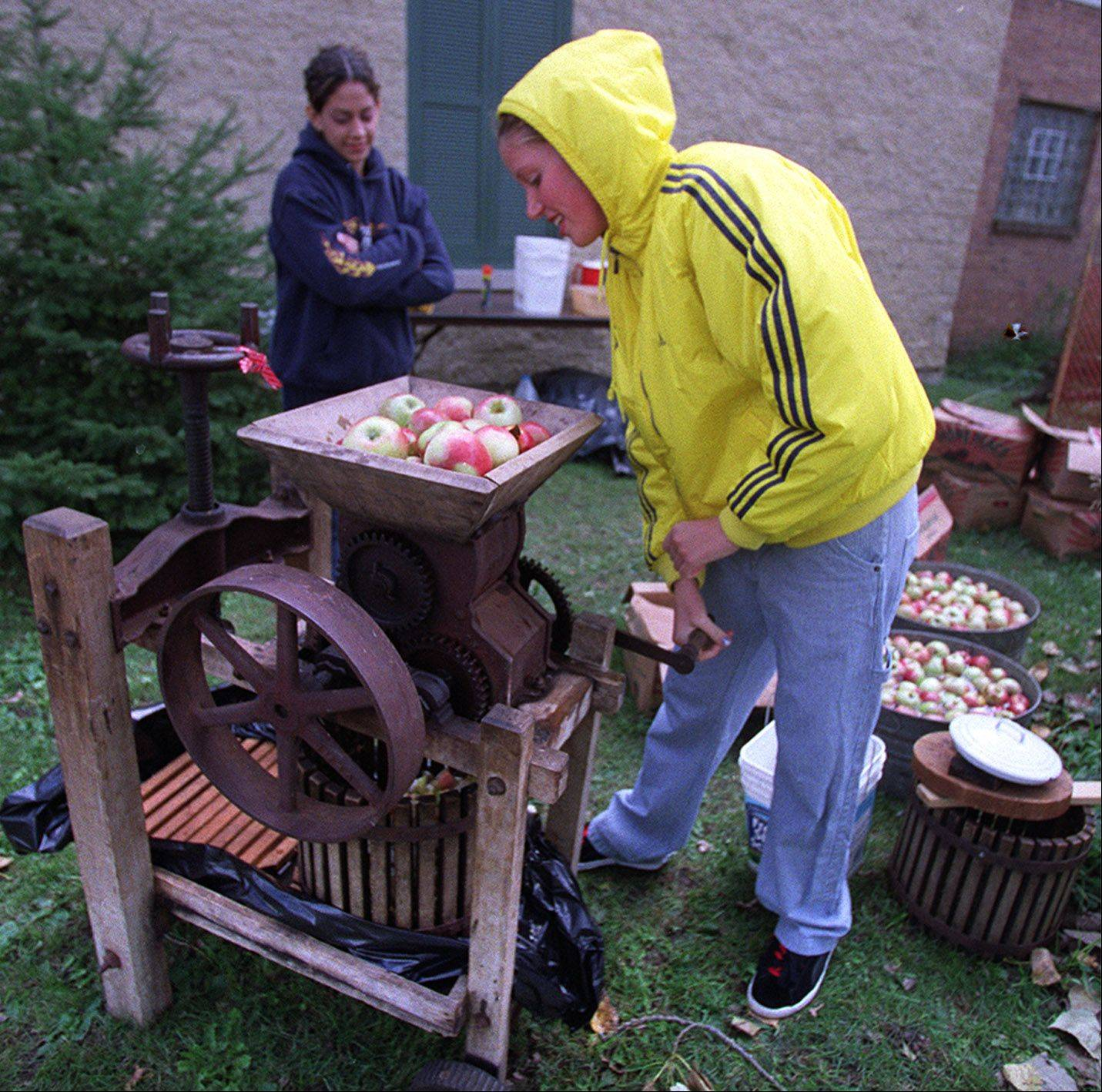 Visitors to McHenry County Historical Society's Cider Fest can watch how apples are ground up to make cider.