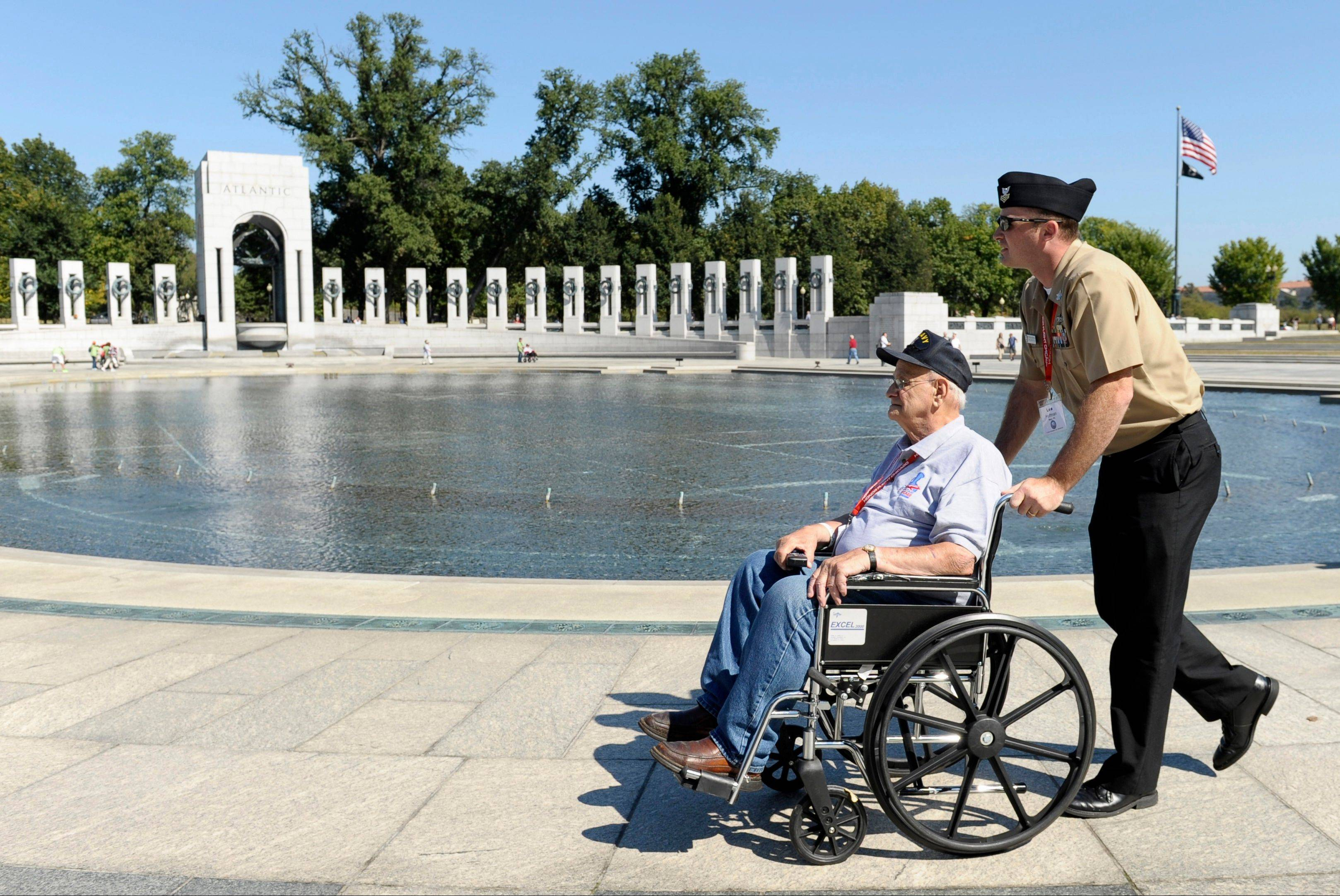 World War II veteran Gus Nicholas of Glendale Heights is pushed by Navy Petty Officer First Class Lee Hoffman on Wednesday as they visit the World War II Memorial in Washington, D.C. Nicholas came to Washington on an Honor Flight despite the shutdown of the federal government.