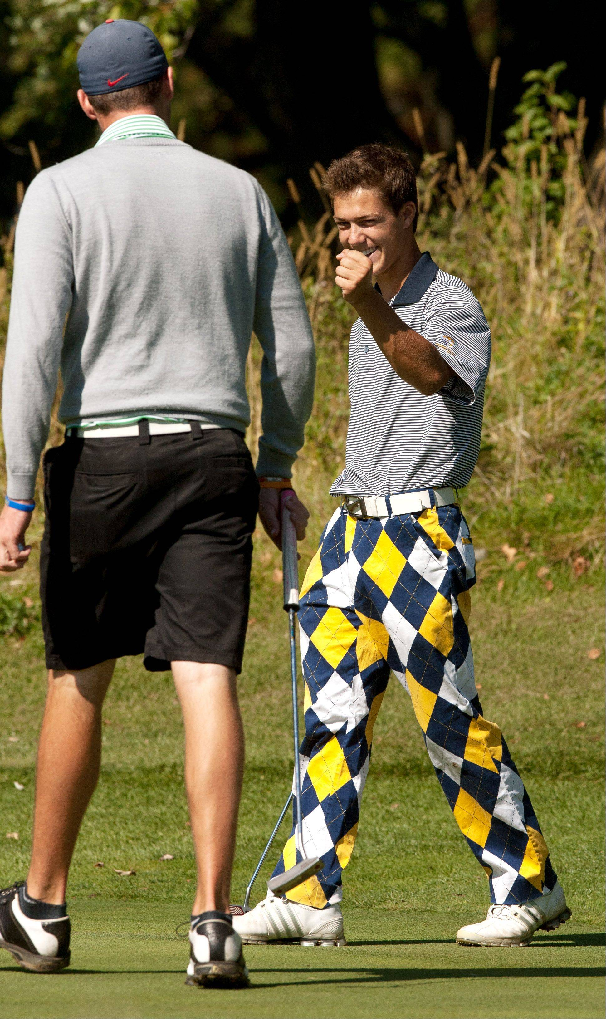Neuqua Valley's Drew Rouches, right, reacts to sinking a 35 foot putt as he high fives Waubonsie Valley's Jason Marrs, during the Upstate Eight Conference boys golf tournament at St. Andrews Country Club in West Chicago.