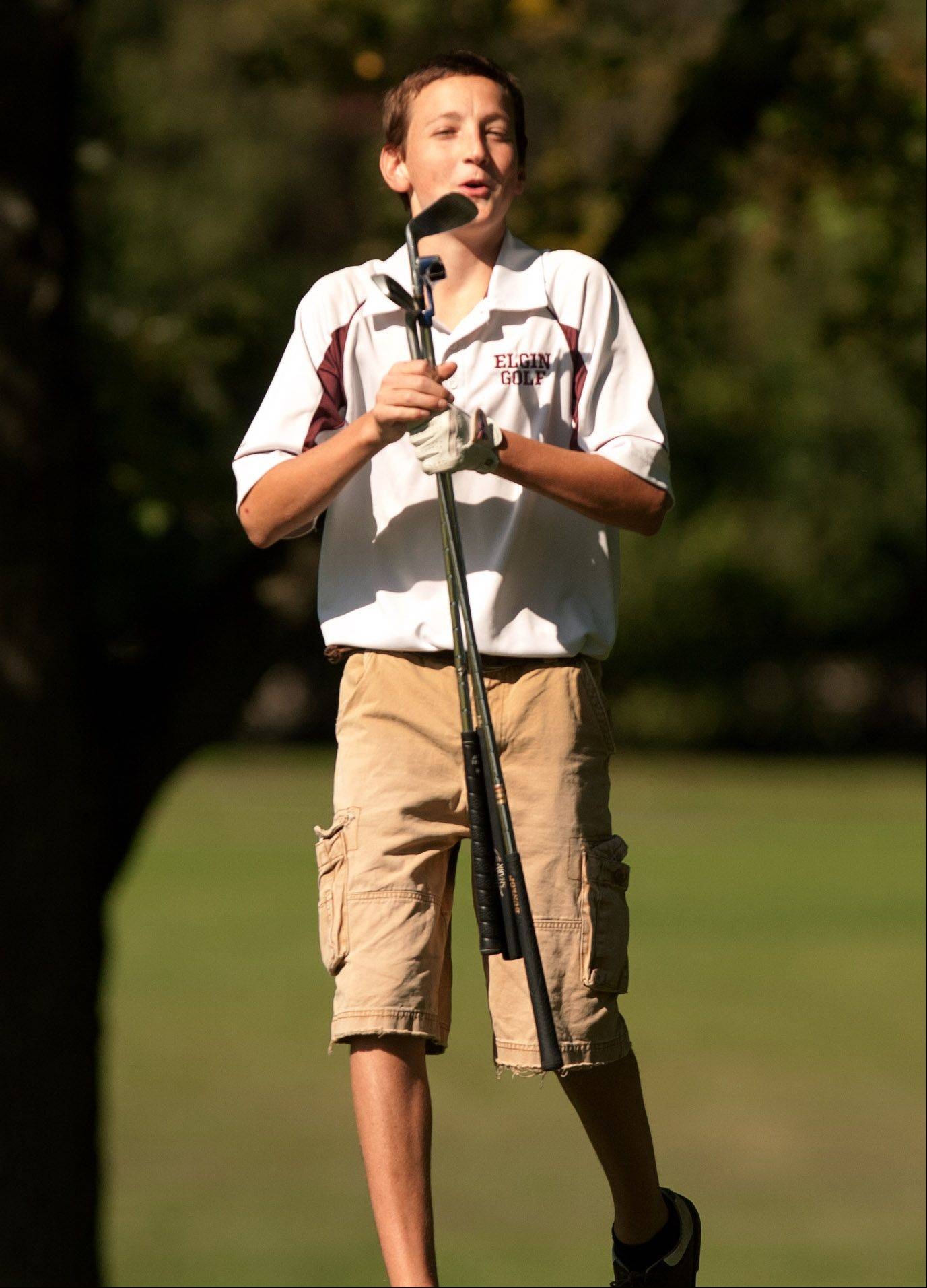 As he gathers his clubs, Elgin's Josh Hegel reacts to sinking a 35 foot putt, during the Upstate Eight Conference boys golf tournament at St. Andrews Country Club in West Chicago.