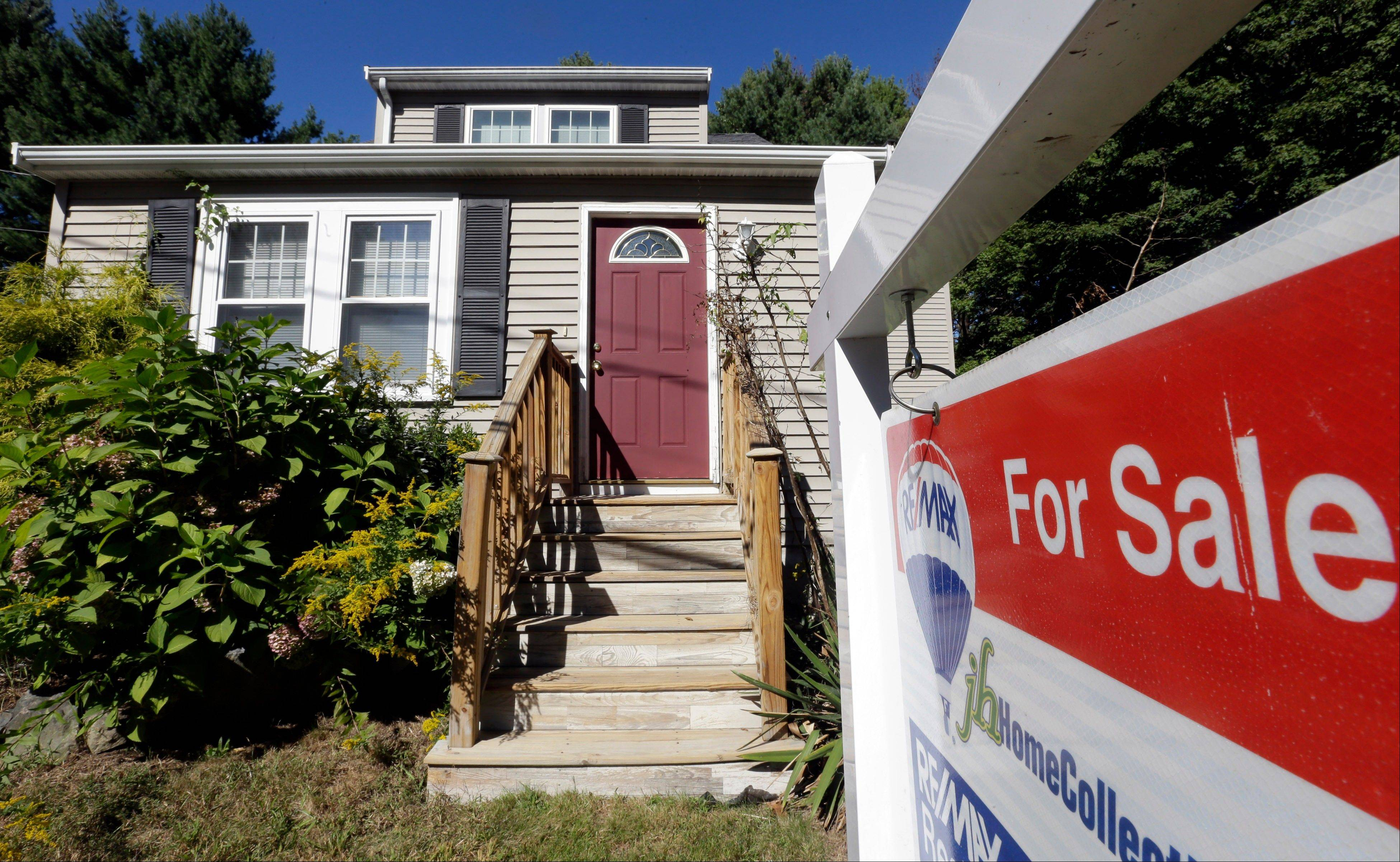 A for sale sign hangs in front of a house in Walpole, Mass. Average U.S. rates on fixed mortgages fell for the third straight week to their lowest point in three months, as a decline in consumer confidence and the onset of the government shutdown forced rates down.