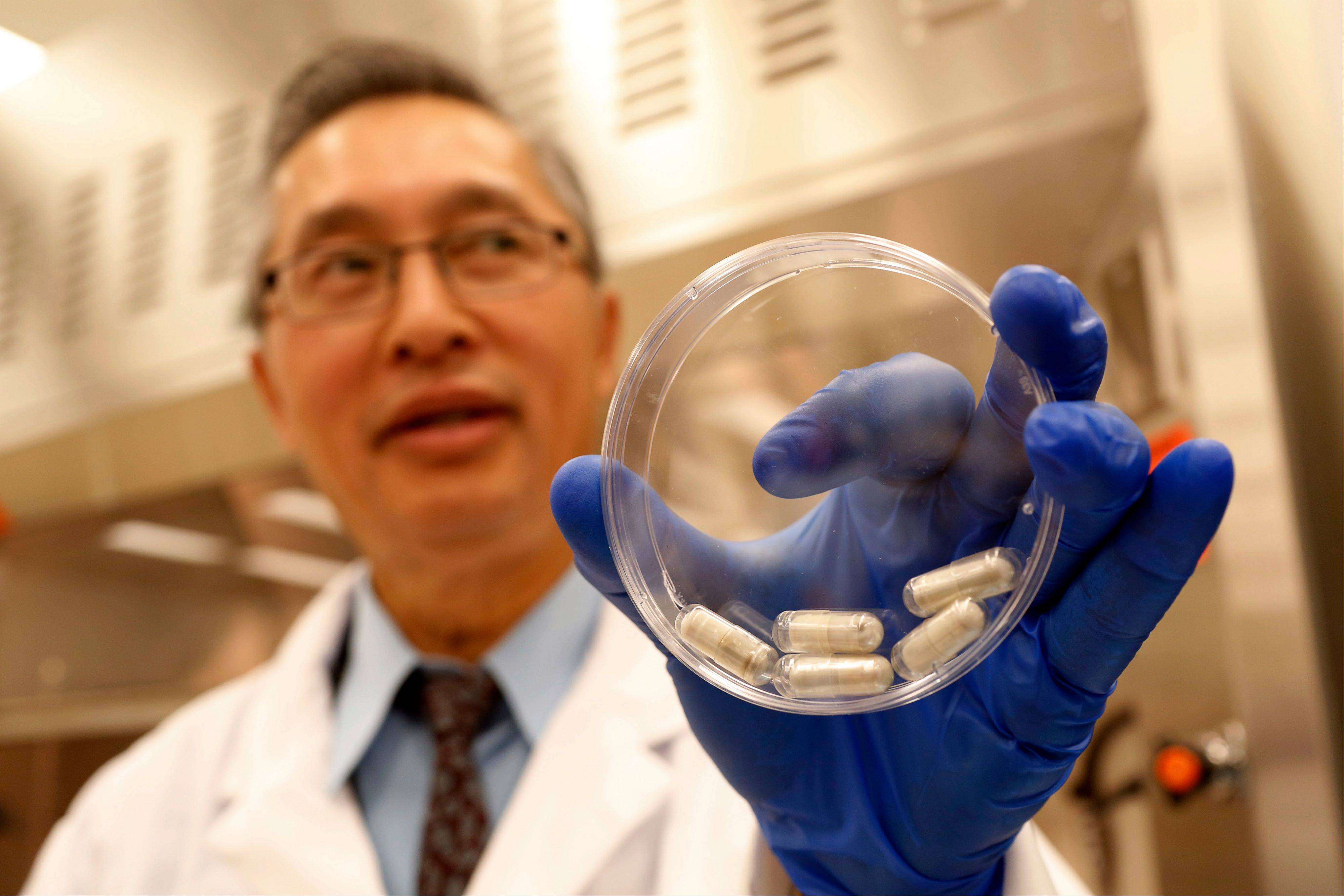 Dr. Thomas Louie, an infectious disease specialist at the University of Calgary, holds a container of stool pills in triple-coated gel capsules in his lab in Calgary, Alberta, Canada .