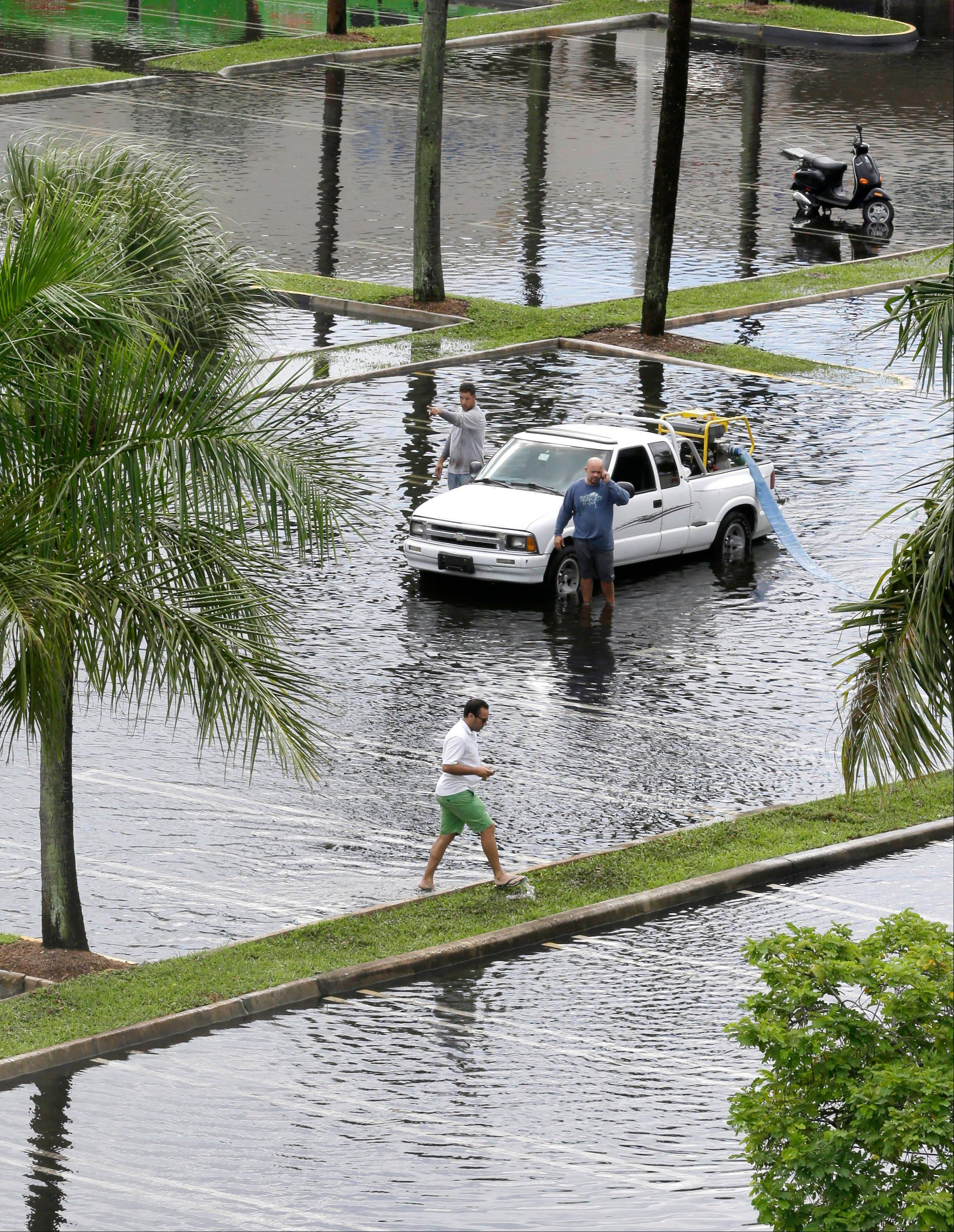 Workers pump water from the parking lot of a shopping center Thursday, after heavy rains in Pinecrest, Fla., a suburb of Miami. Preparations began Thursday along the central Gulf Coast as newly formed Tropical Storm Karen approached.