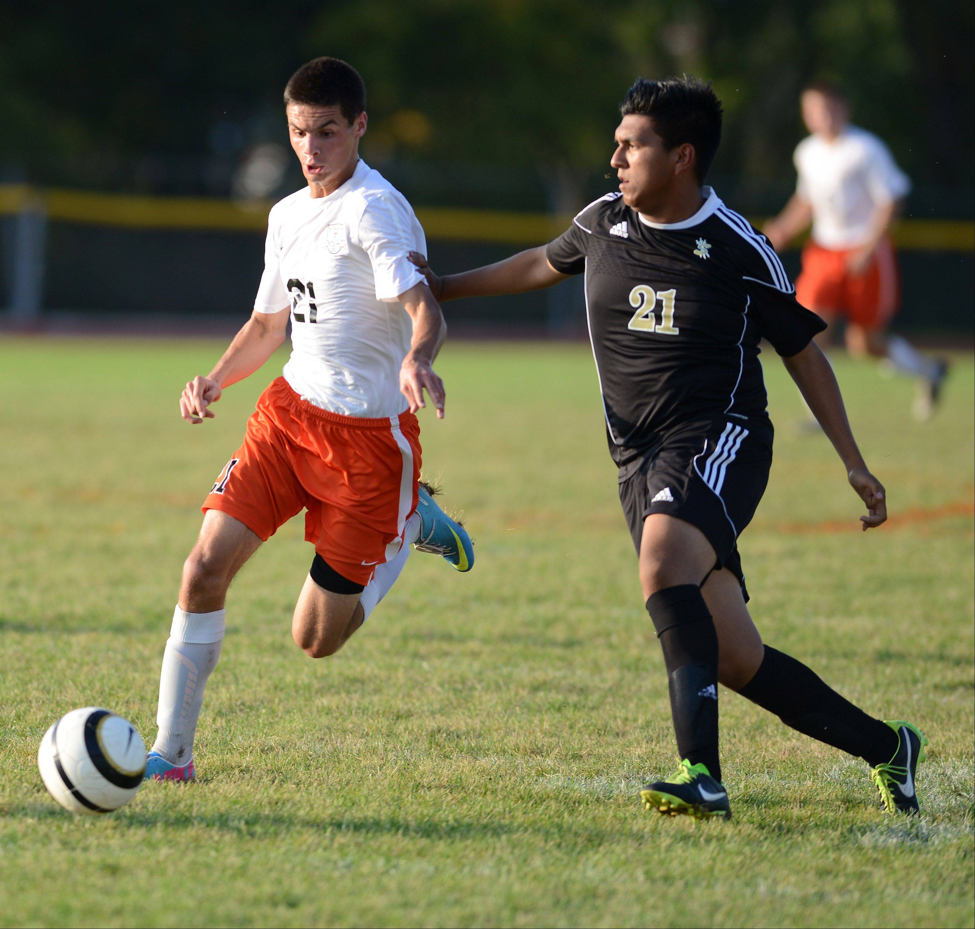 St. Charles East�s Daniel DiLeonardi brings the ball upfield while being defended by Streamwood�s Manny Carrillo during Thursday�s game in St. Charles.