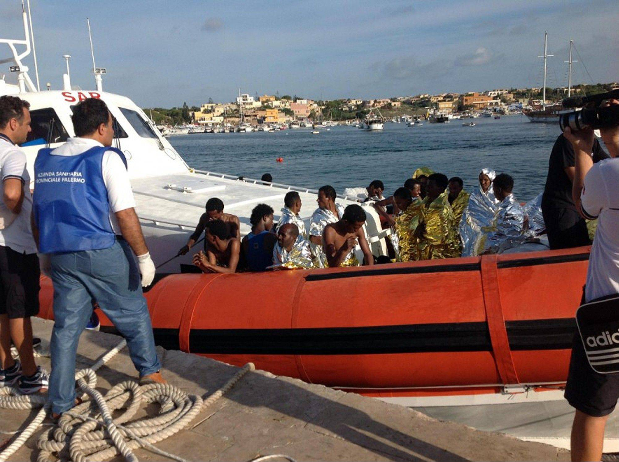 An Italian Coast Guard boat carries rescued migrants as they arrive in the port of Lampedusa Thursday. A ship carrying African migrants to Europe caught fire and capsized off the Italian island of Lampedusa Thursday, killing at least 114 people as it spilled hundreds of passengers into the sea.