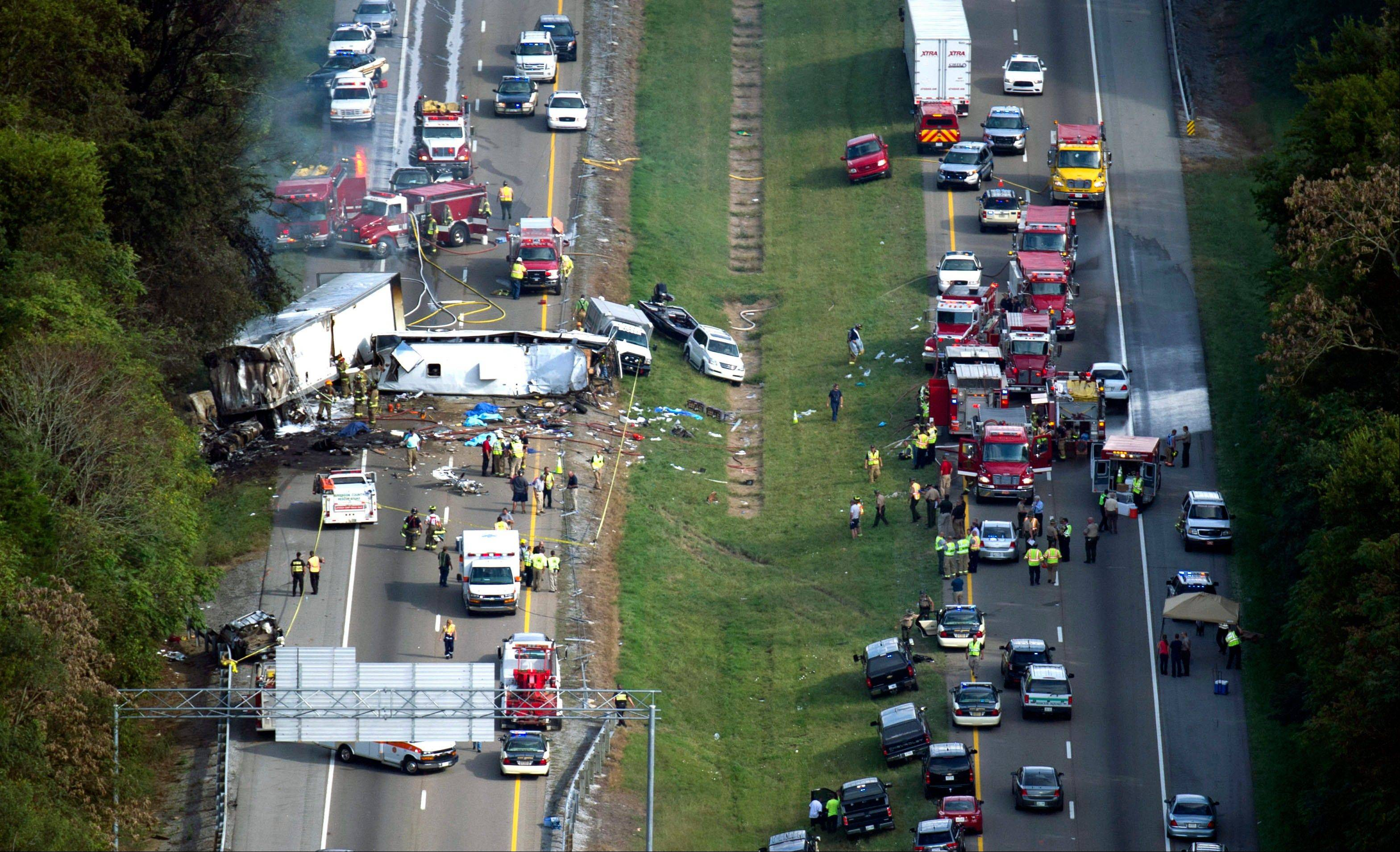 In this aerial photo, emergency workers respond to a crash involving a passenger bus, a tractor-trailer and an SUV near Dandridge, Tenn., on Wednesday, Oct. 2, 2013. Authorities said the bus, carrying members of a North Carolina church group, veered across the highway median and crashed into the other vehicles in a fiery wreck that killed eight people.