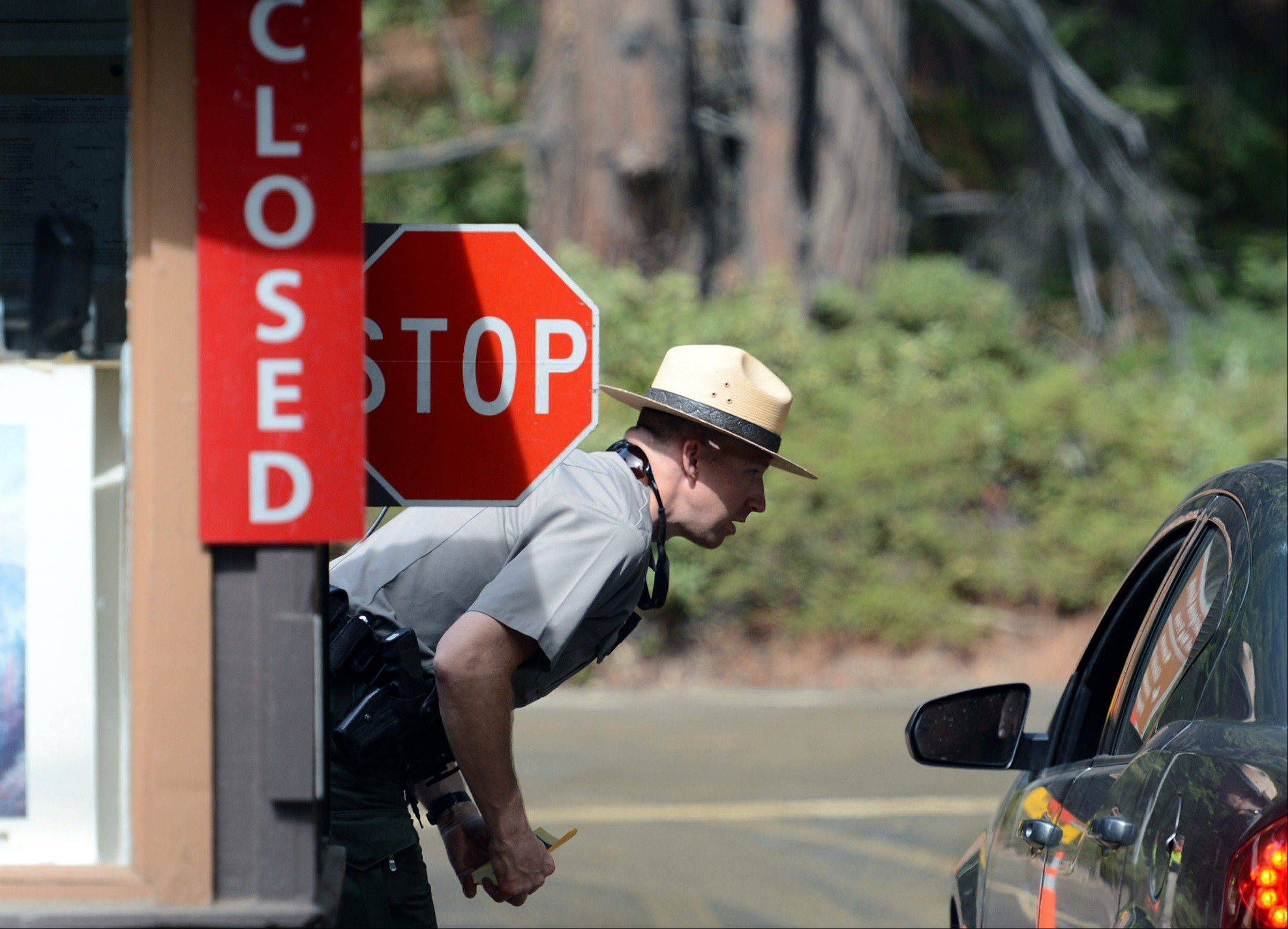U.S. park ranger Jeff Gardner informs visitors of the closure of Yosemite National Park, Calif., of the closure of the park due to the government shutdown.