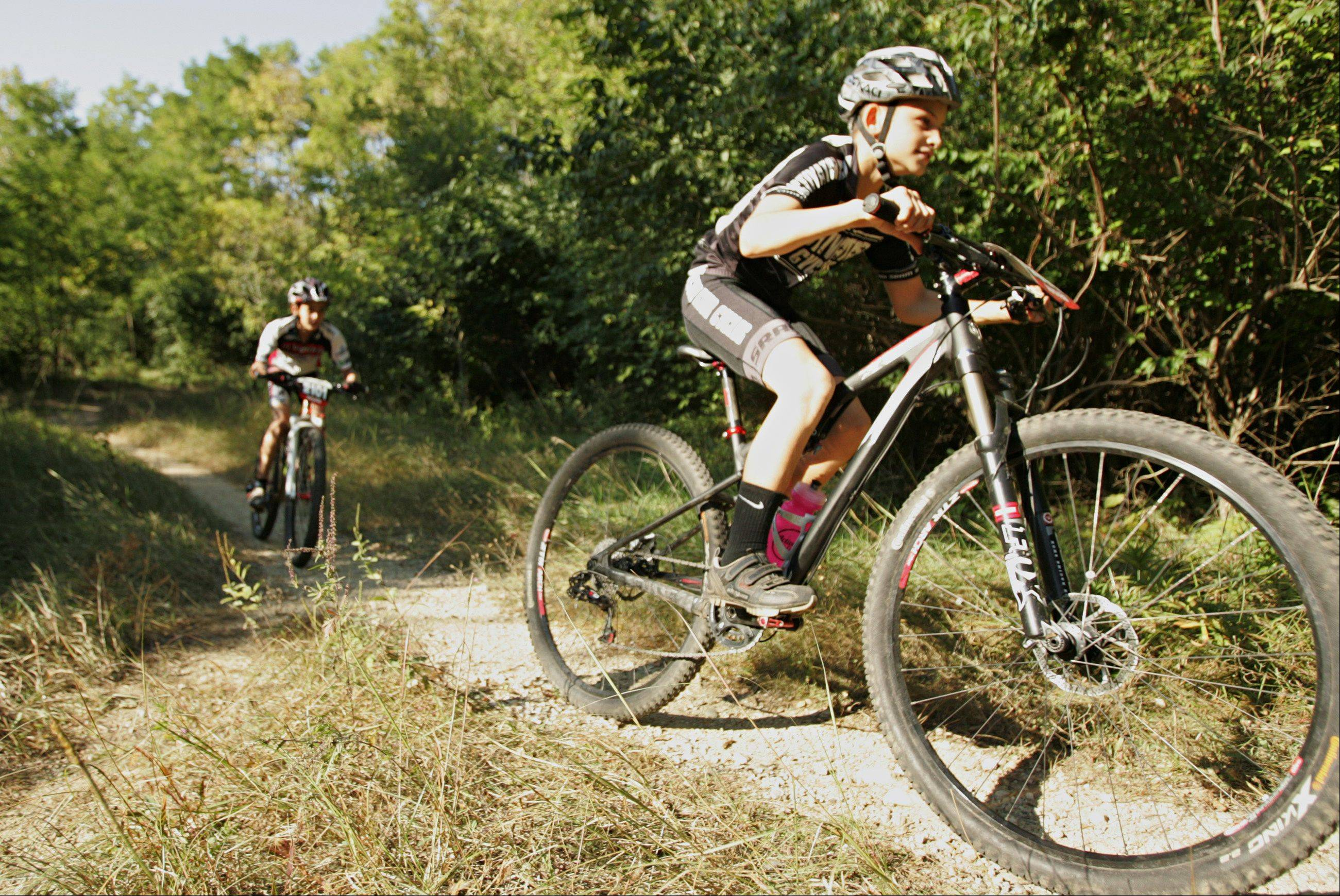 Mountain bike riders Will Darling, 11, of Vernon Hills, front, and Nate Knowles, 12, of Batavia, were introduced to the sport by their fathers. USA Cycling ranks Nate second and Will third in their age group in the cross-country mountain biking category.