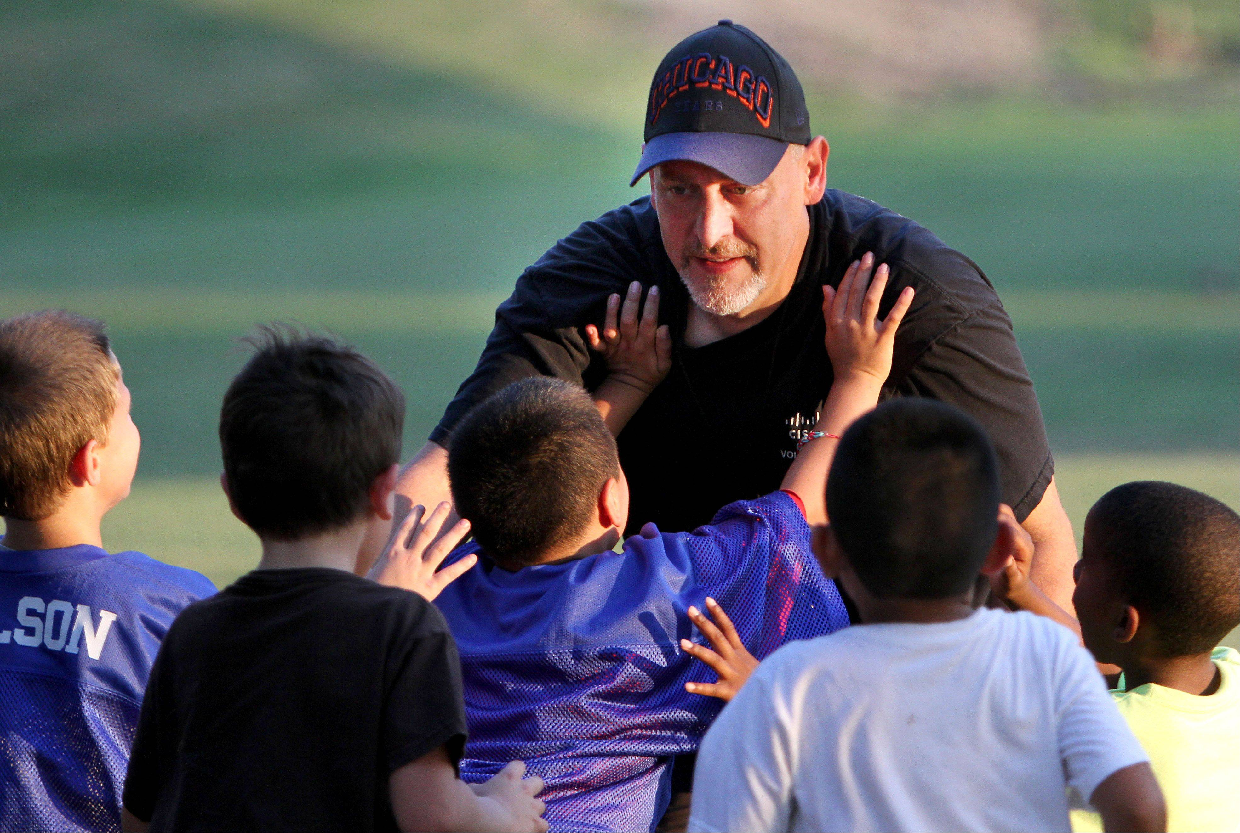 Paul Metcalf of Lake Zurich runs through drills with kids on the Ela Junior Bears youth football team at Knox Field in Lake Zurich. The team has opened to children who previously could not afford to join a youth sports team.