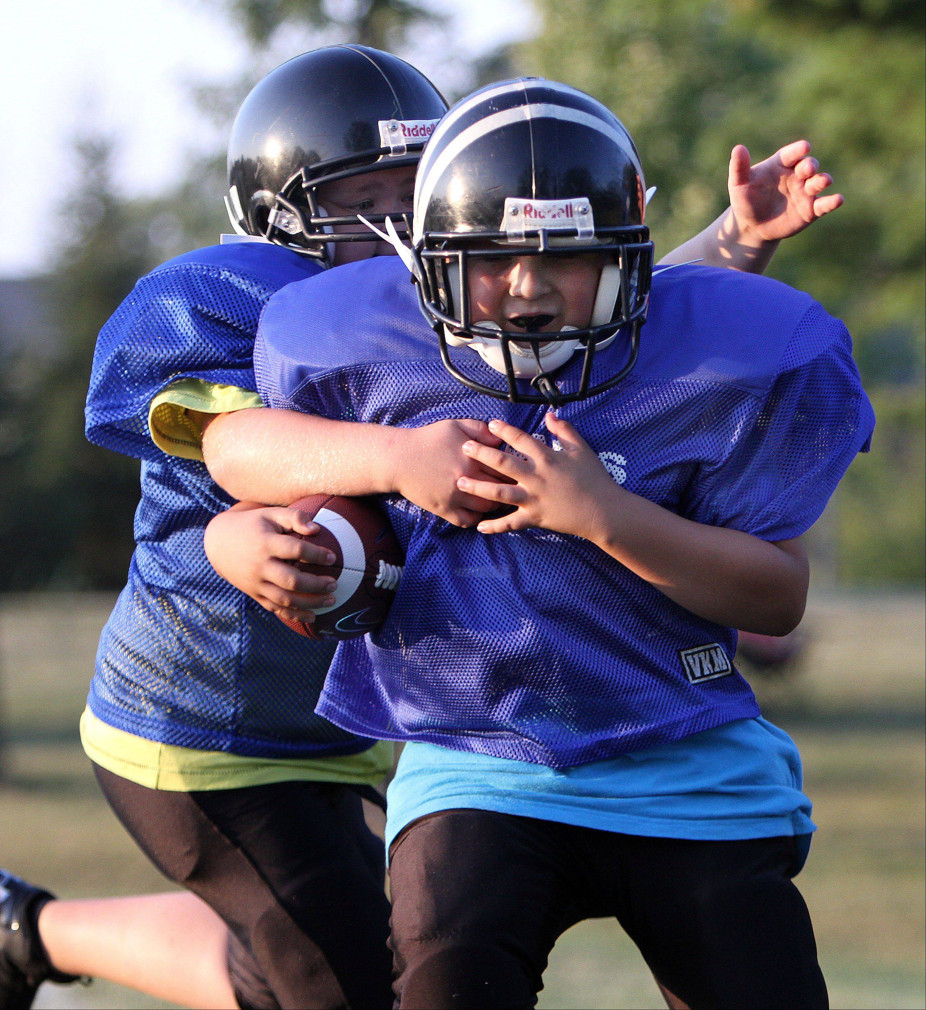 Christian Ponce, right, and Andre Neydenov, both 10 and from Lake Zurich, run through a tackling drill as the Ela Junior Bears youth football team practices at Knox Field in Lake Zurich.