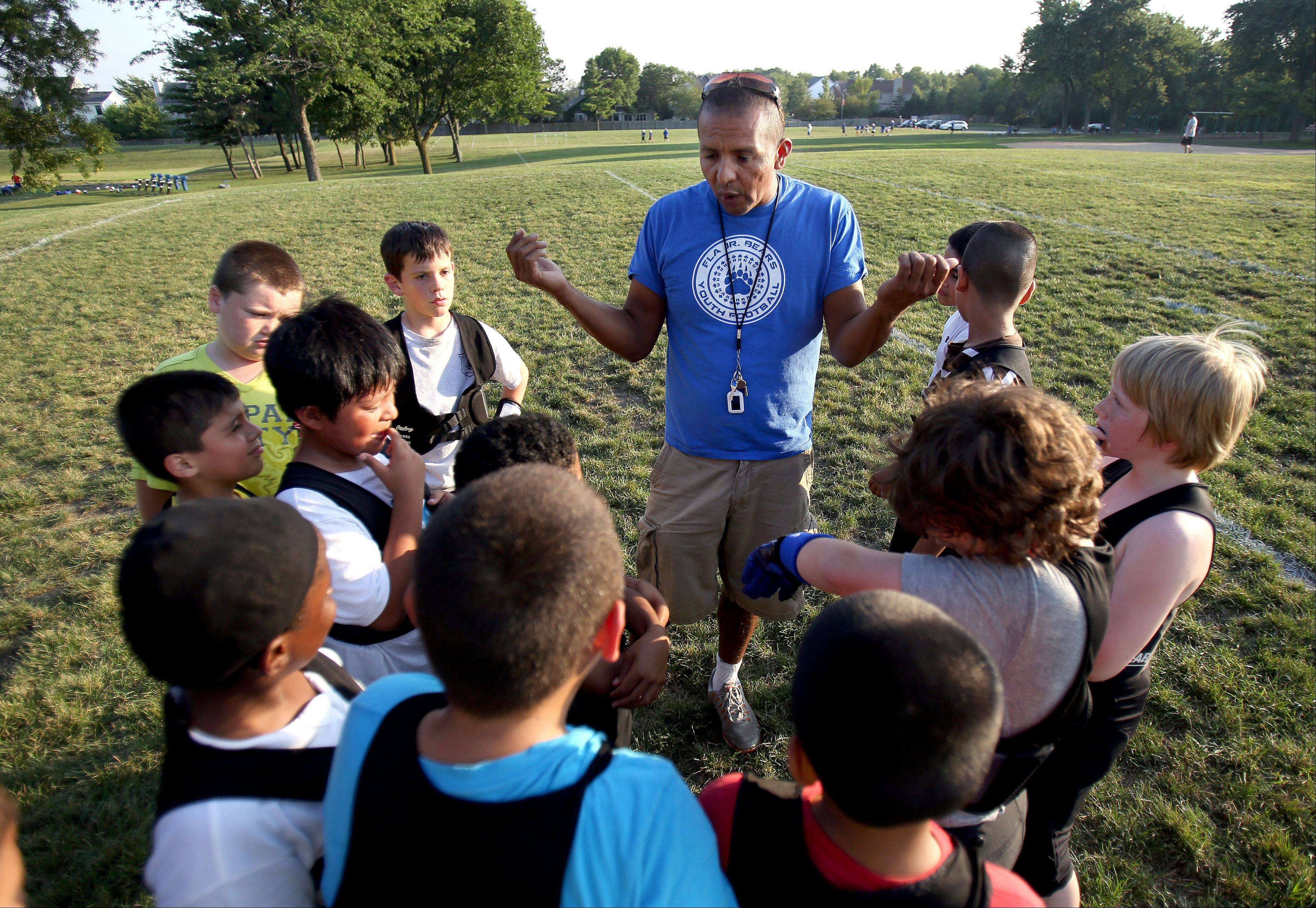 Wil Juarez, vice president of the Ela Junior Bears youth football team, talks to his players during practice at Knox Field in Lake Zurich.