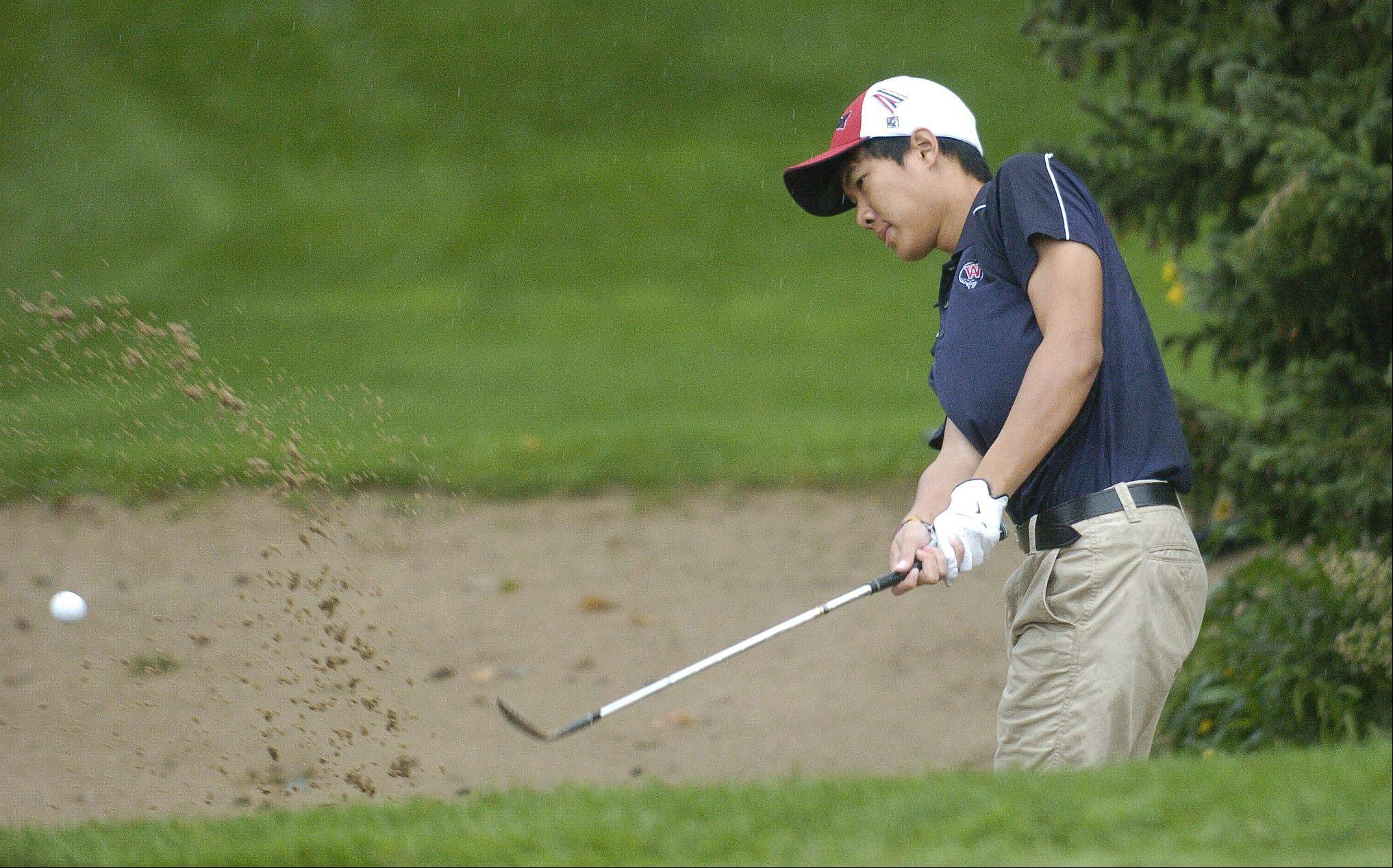West Aurora's Piya Teerakanog blasts out of the sand on the 16th hole. Rain briefly halted play in Bartlett Thursday at a DuPage Valley Conference boys golf tournament at Bartlett Hills Golf course.