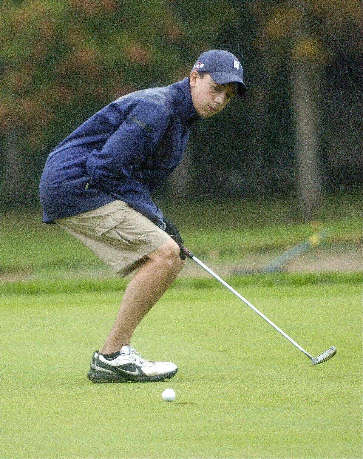 West Aurora's Dean Lavery puts some English onto his 16th hole put. Rain briefly halted play in Bartlett Thursday at a DuPage Valley Conference boys golf tournament at Bartlett Hills Golf course.