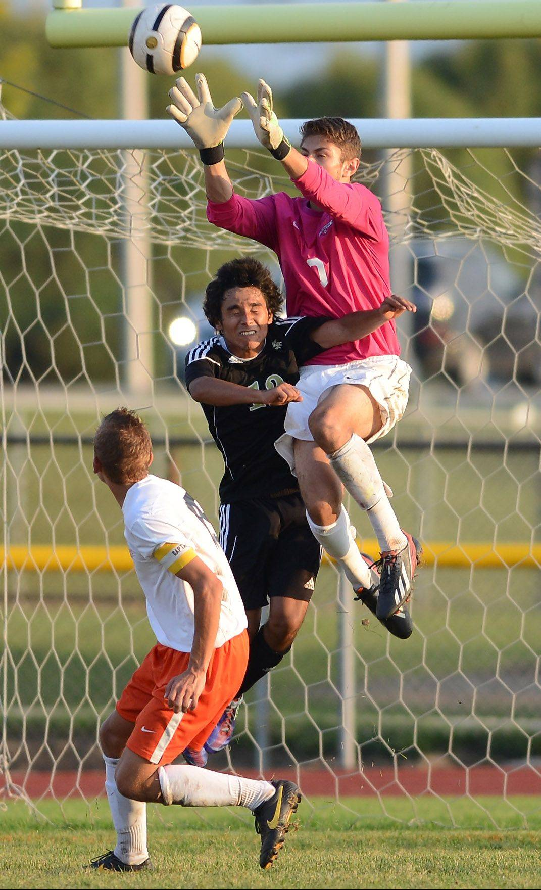 St. Charles East goalkeeper Chri Lucatorto snares ball while being challenged by Streamwood's Brain Benitez during Thursday's game in St. Charles.