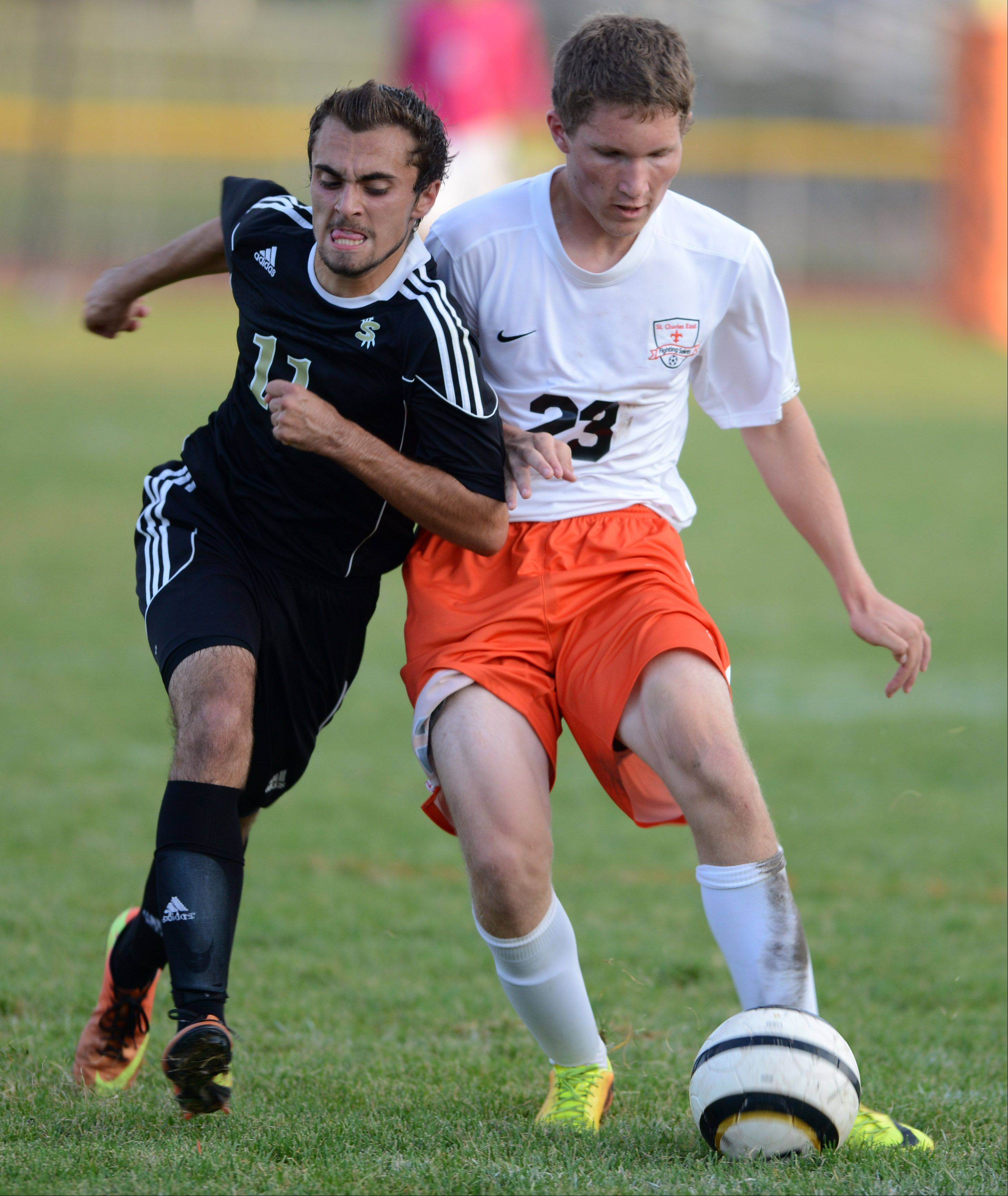 Streamwood's Brandon Malpartida battles St. Charles East's Tyler Robbins for the ball during Thursday's game in St. Charles.