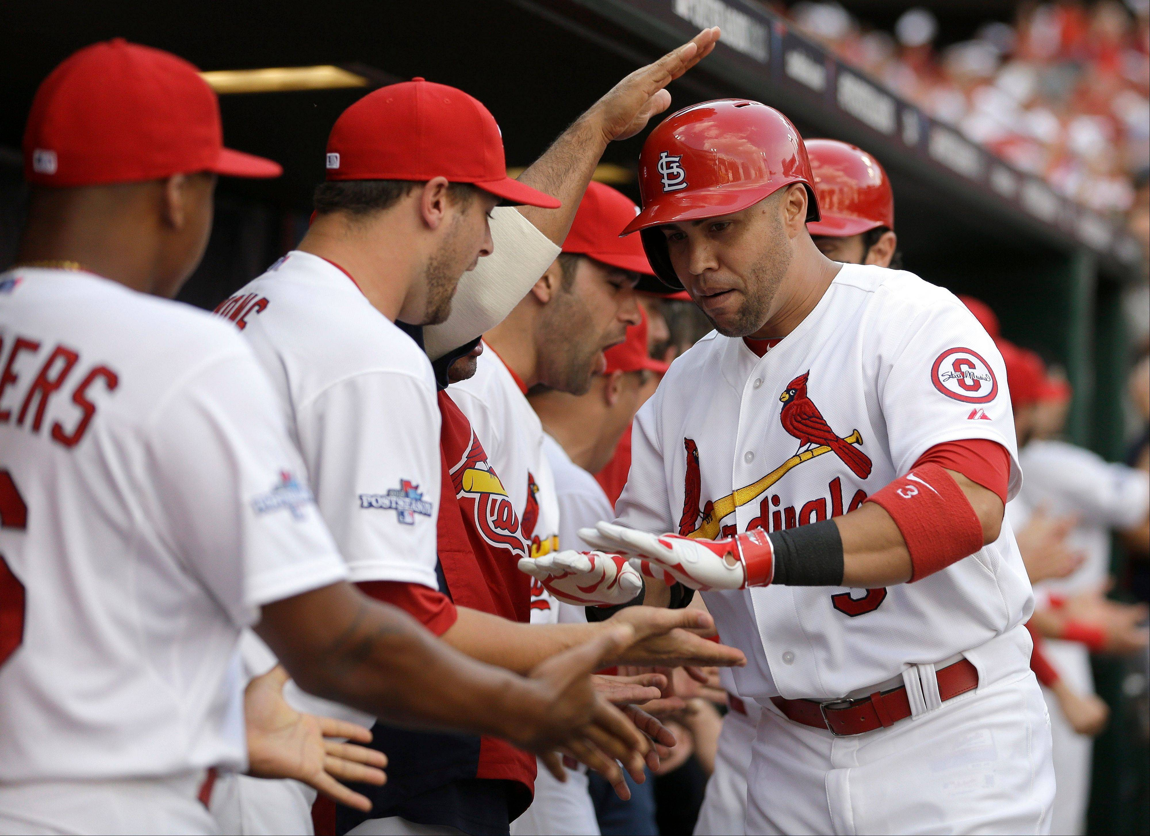 St. Louis Cardinals' Carlos Beltran, right, is congratulated in the dugout by teammates after hitting a three-run home run against the Pittsburgh Pirates in the third inning of Game 1 of baseball's National League division series on Thursday, Oct. 3, 2013, in St. Louis.