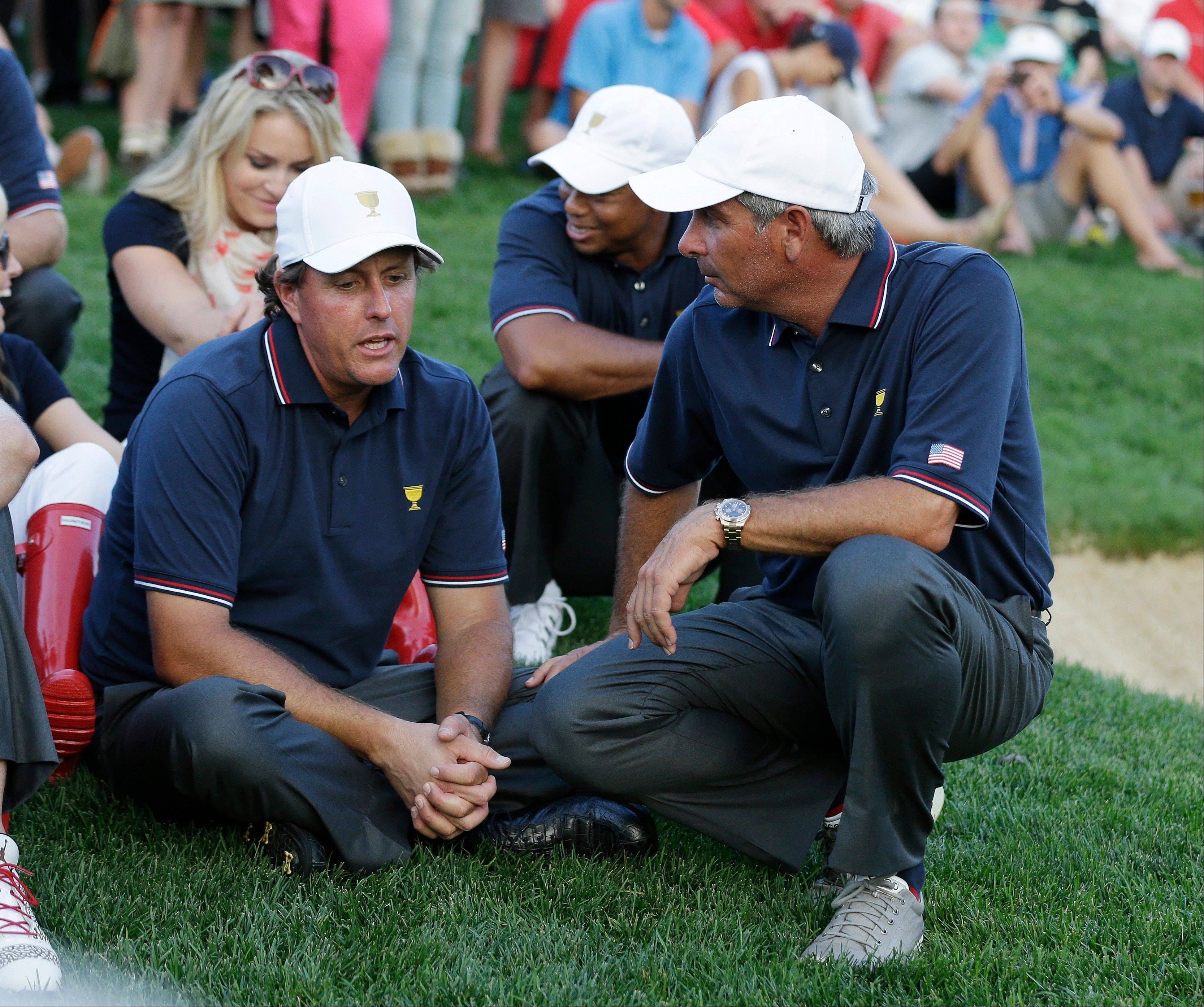U.S. team captain Fred Couple, left, talks to Phil Mickelson during a four-ball match Thursday at the Presidents Cup golf tournament at Muirfield Village Golf Club in Dublin, Ohio.